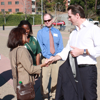 Joan Kennedy shaking hands with Gavin Newsom on Cal Poly's campus