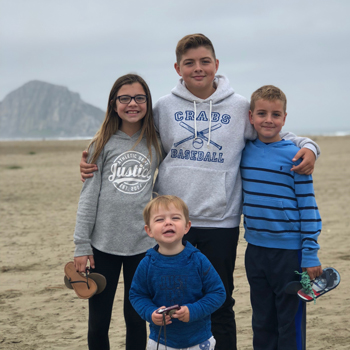 Lindsay Christiansen's four children smiling in front of Morro Rock.