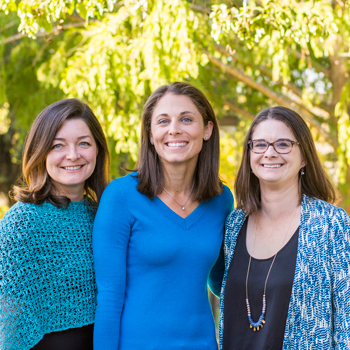 Educators Dr. Tanya Flushman, Dr. Megan Guise and Dr. Briana Ronan smile on O'Neill Green at Cal Poly