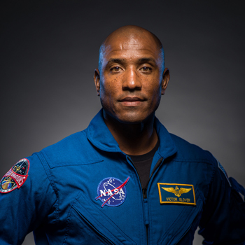 Victor Glover stands in his flight suit