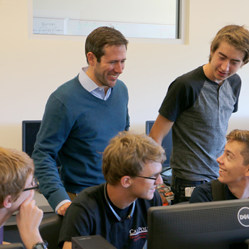 Zachary Peterson instructs a group of five students in a computer lab
