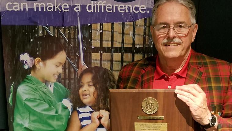 Alumnus Matt Gregory holds an awards plaque.