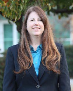 Alumna Kelle Schoeder poses in a blue blazer.