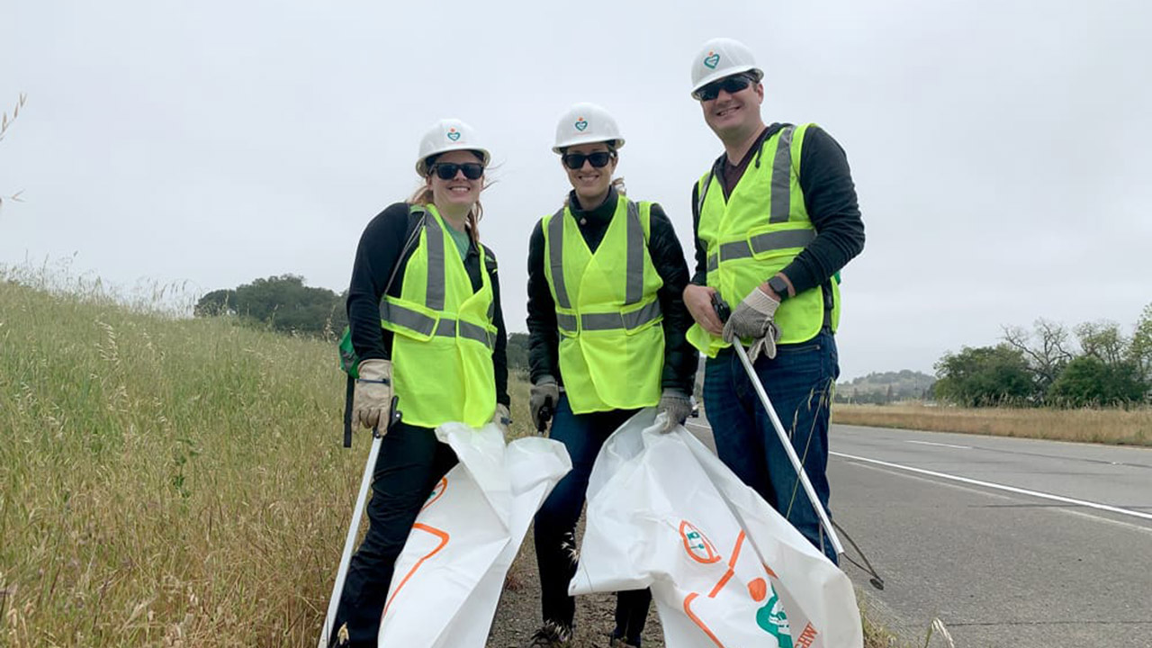 Three members of Cal Poly's North Bay Chapter clean up a stretch of Highway 101