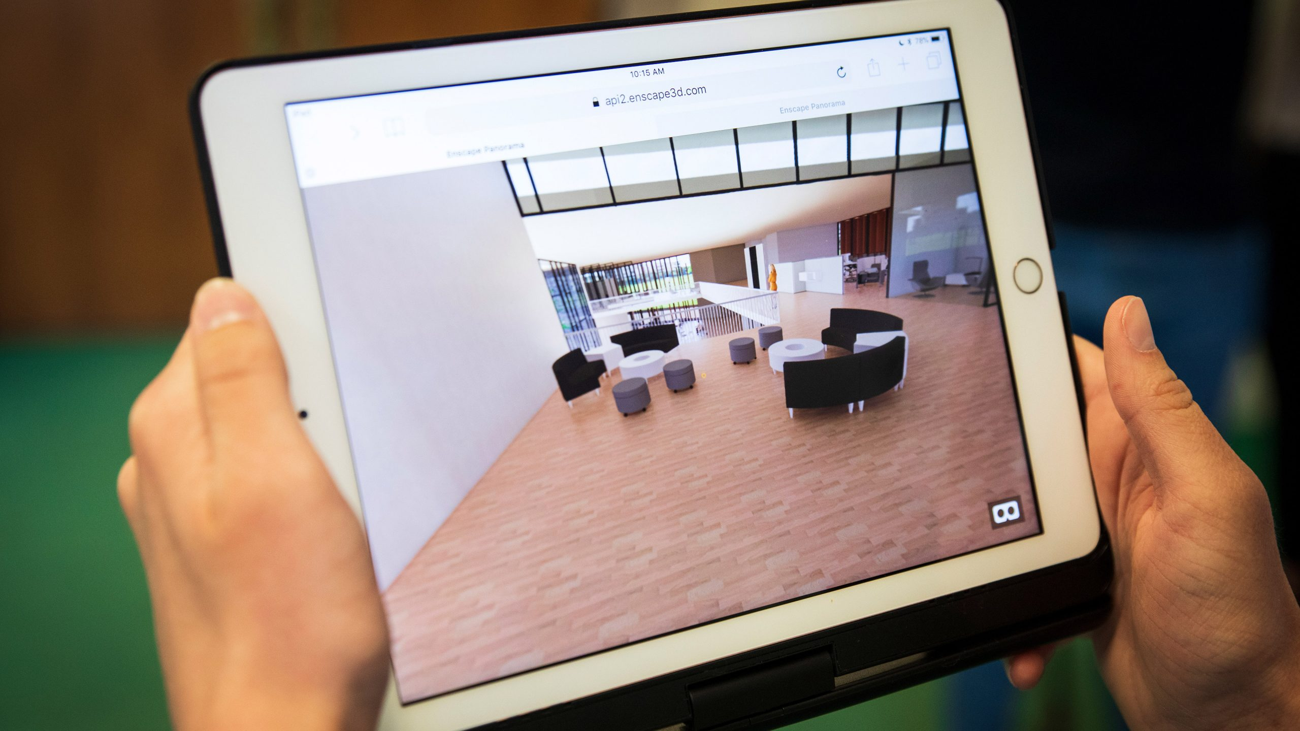 Hands holding a tablet displaying a student's virtual rendering of a building designed for Paradise, CA. Photo by Joe Johnston.