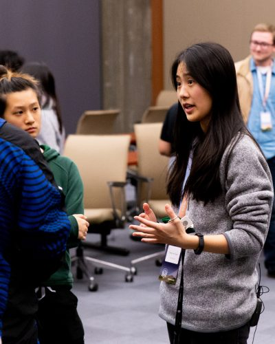 Selynna Sun speaking with hackathon participants at a team mixer