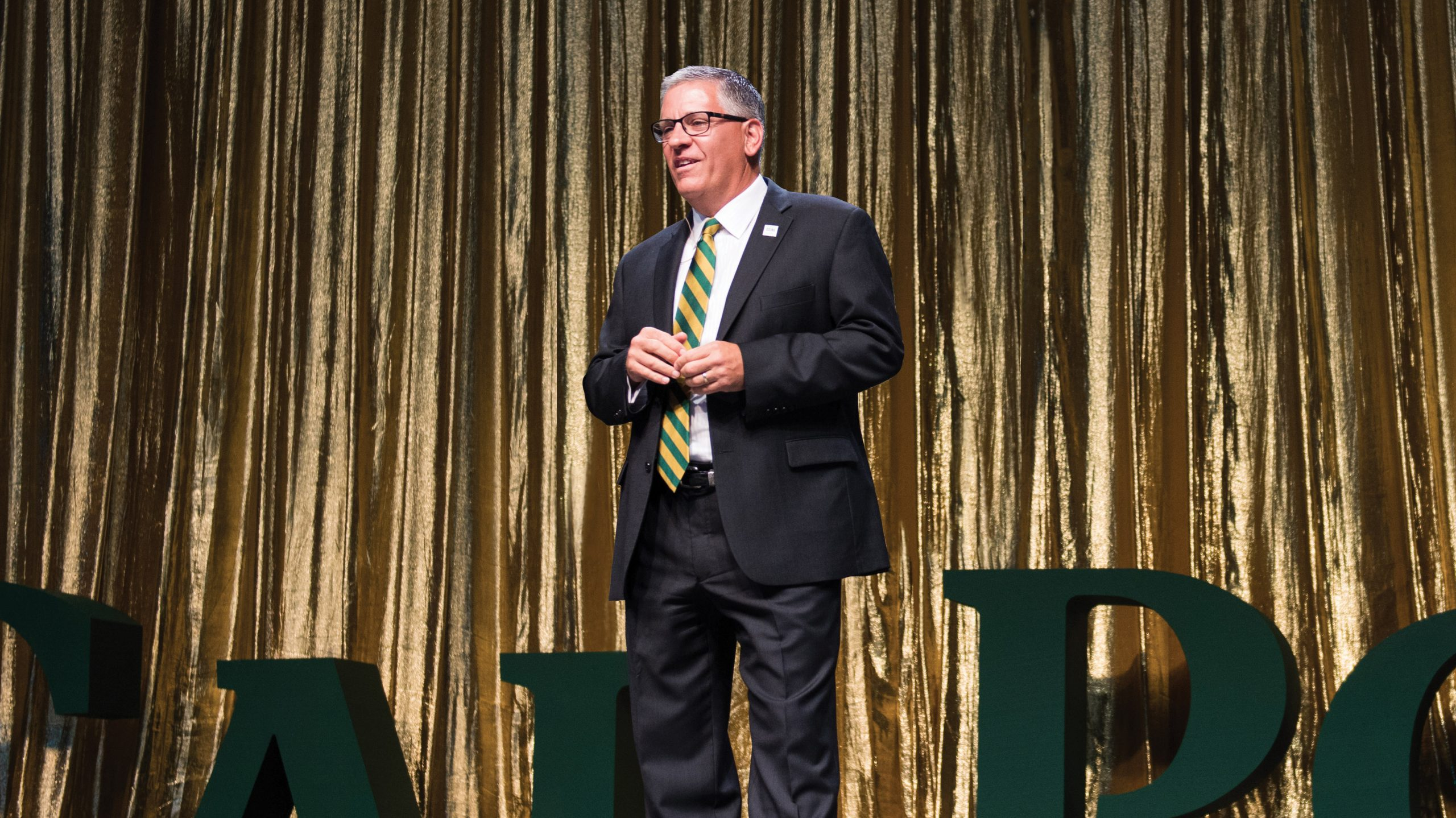 President Armstrong speaks on stage at the Evening of Green and Gold with a Cal Poly sign in the background