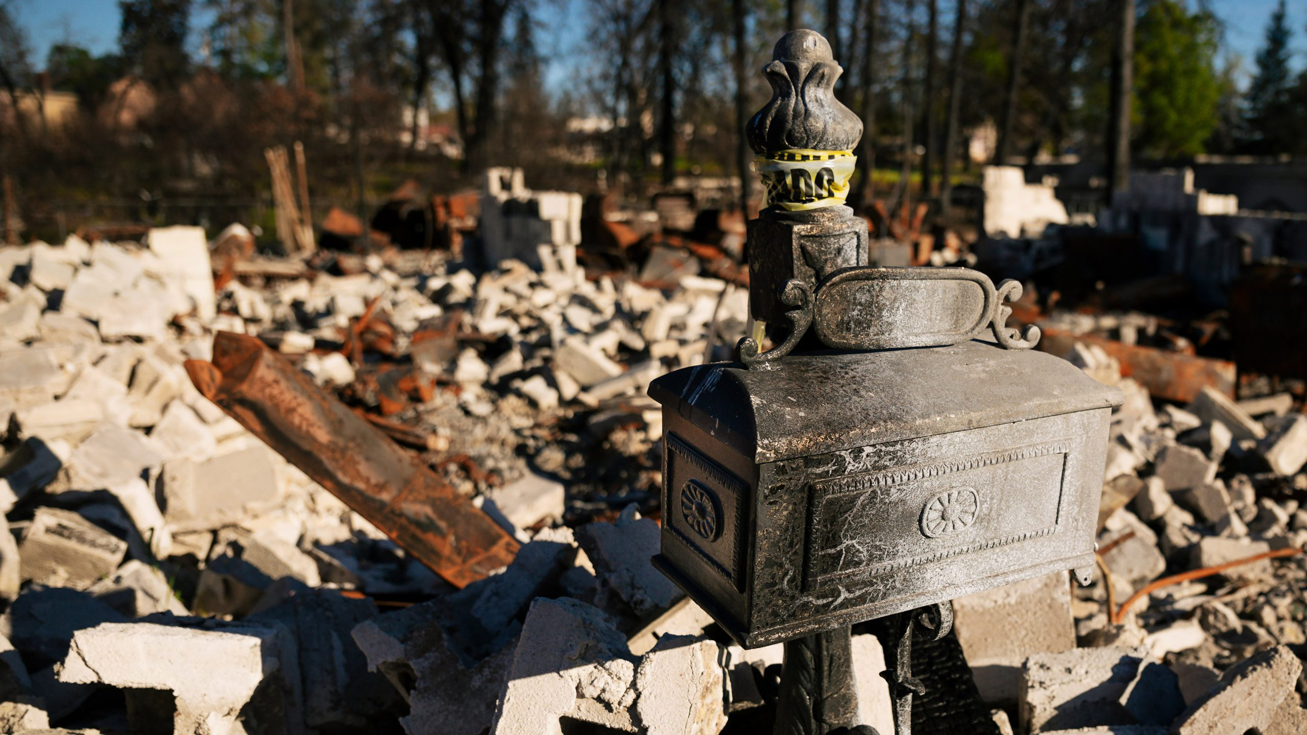 A blistered mailbox stands with a destroyed house in the background in Paradise, CA. Photo by Joe Johnston.