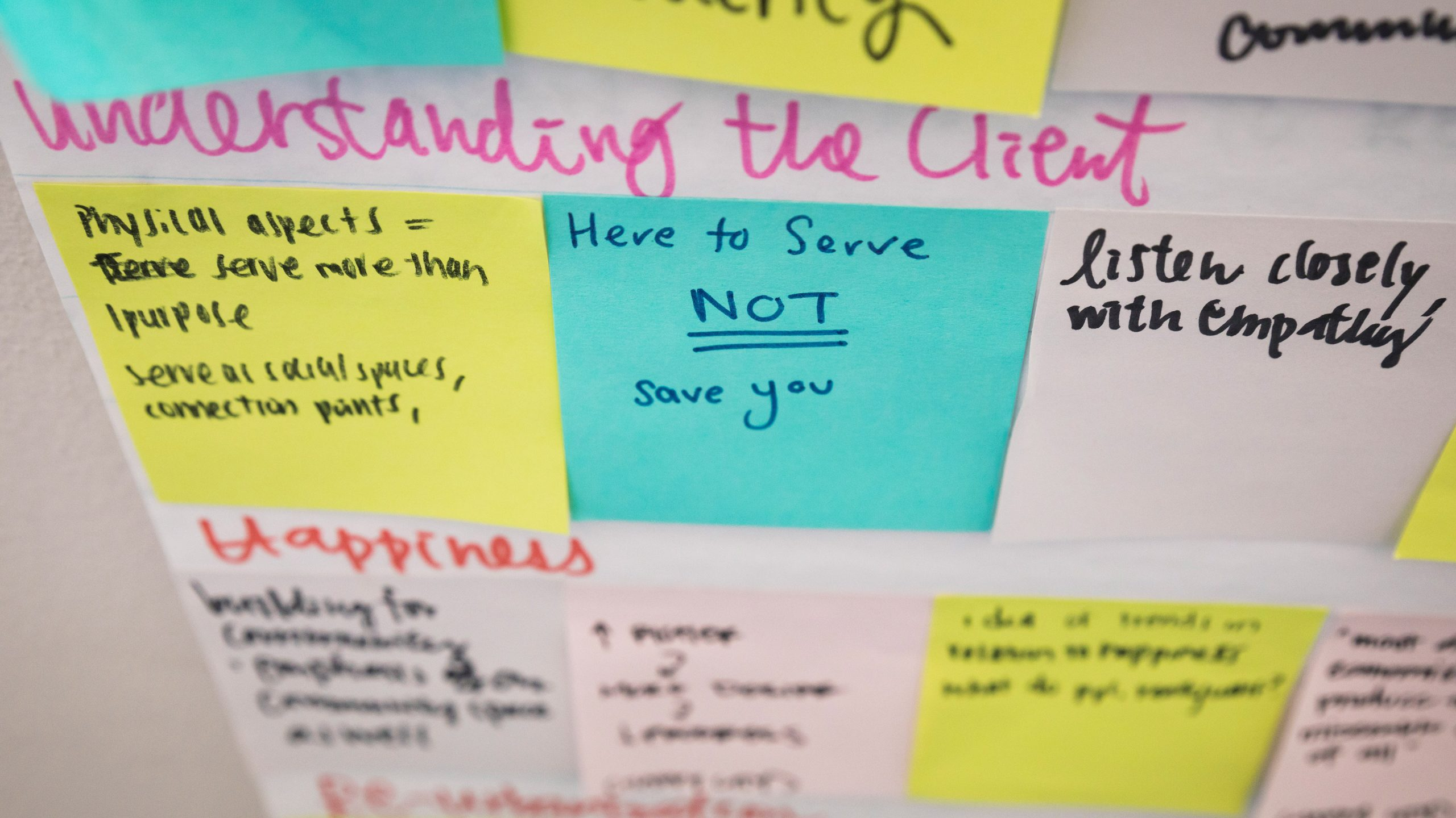 "Post-it notes on the walls of a Cal Poly architecture studio saying ""Here to serve you, not save you."" Photo by Joe Johnston."