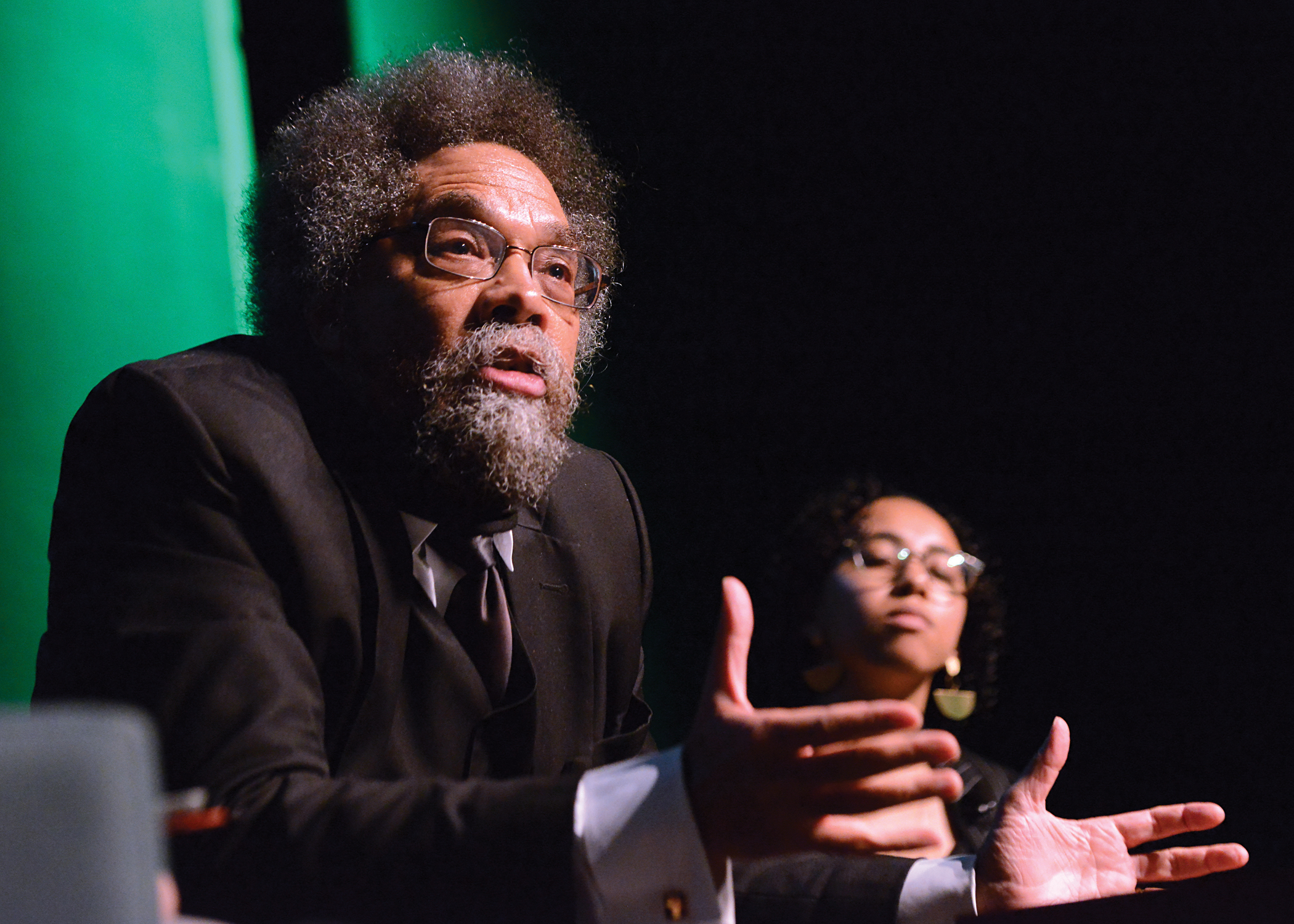 Dr. Cornel West speaks on stage at the Performing Art Center pavillion with student Leilani Hemmings Pallay