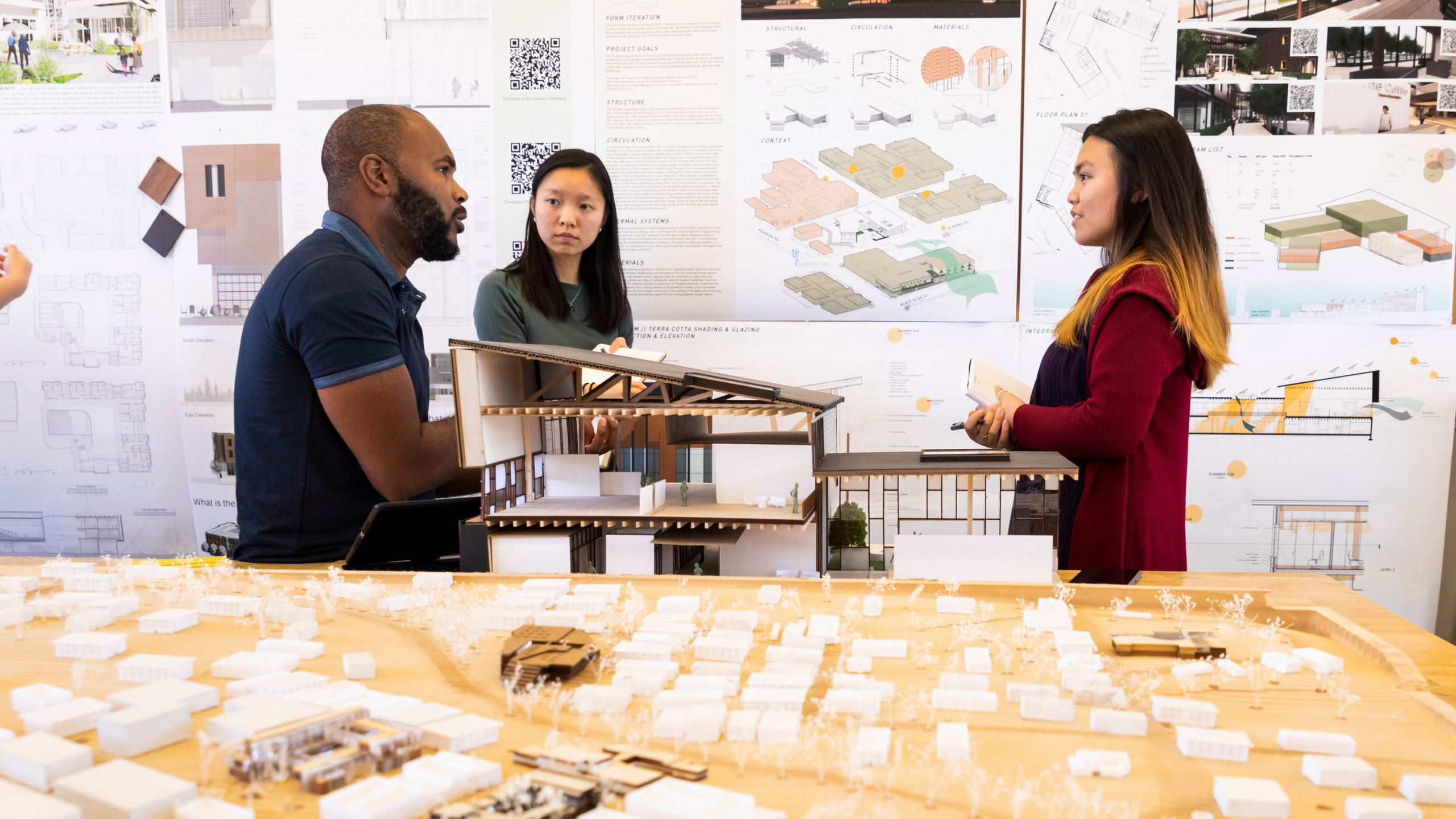 Faculty member Jermaine Washington speaks with two architecture students in front of their final design poster. Photo by Joe Johnston.