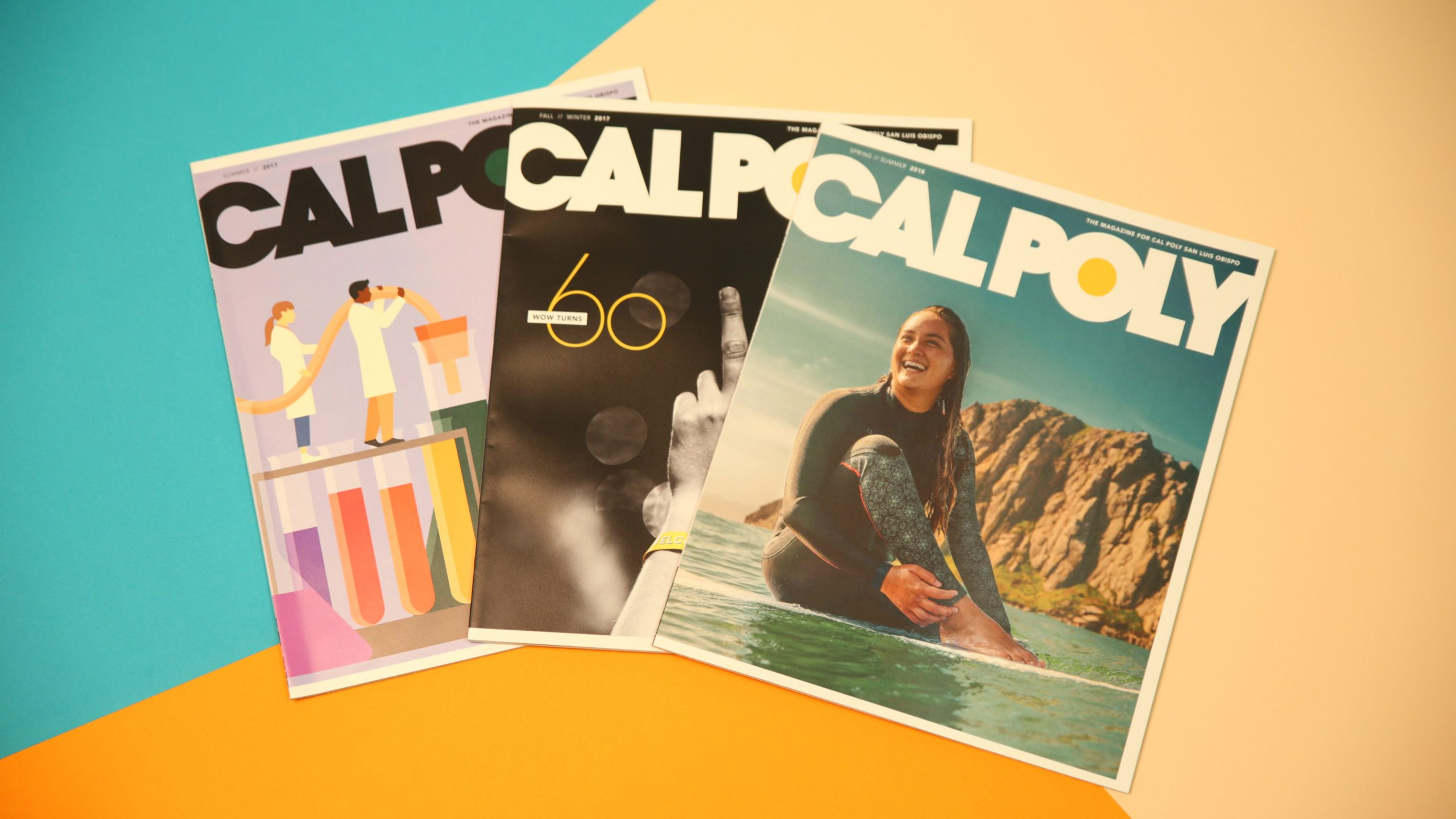 Three issues of Cal Poly Magazine arranges on an orange, blue and creme background.