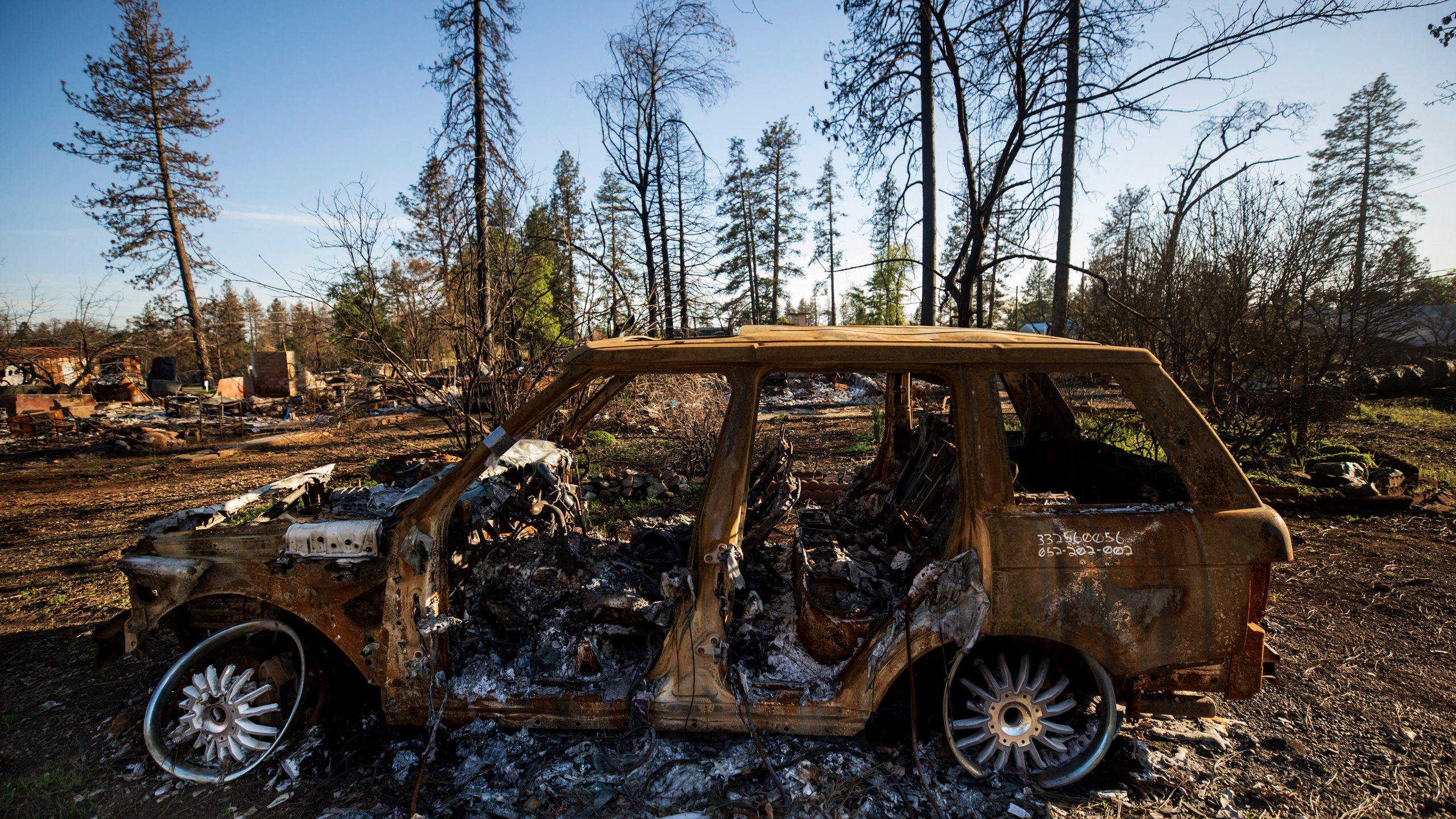 A charred vehicle sits in front of a neighborhood reduced to rubble in Paradise, CA. Photo by Joe Johnston.