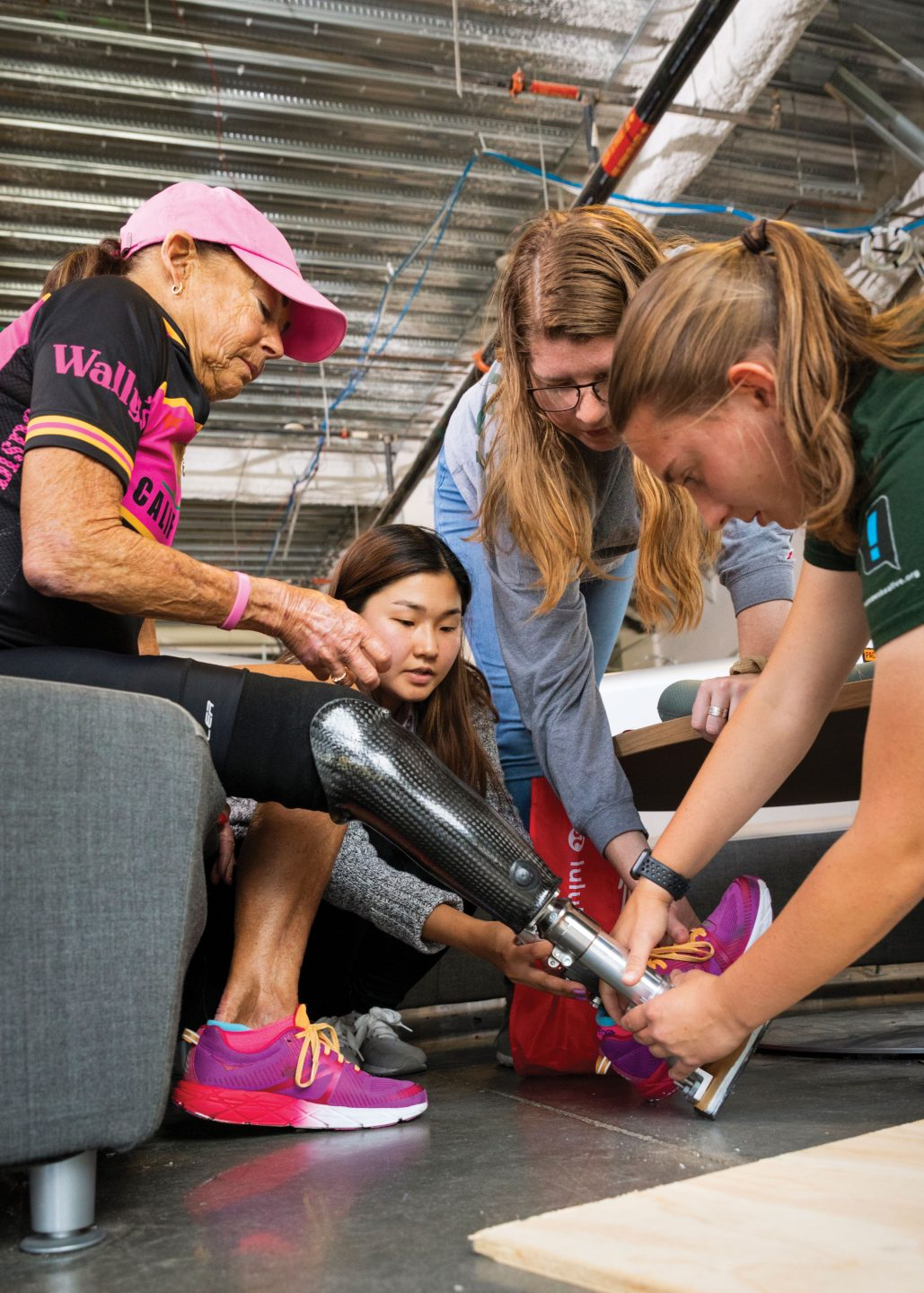 Three female engineering students fit a prosthetic leg onto a local triathlete's right leg in the QL+ lab