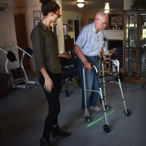 Sidney Collin stands besides Jack Brill as he tests the Gaitway device on his walker in his home