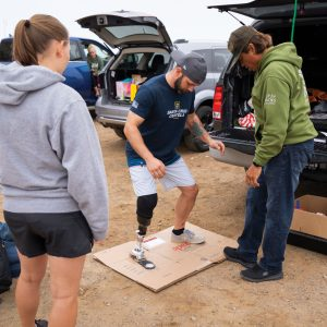 Kyle Kelly tries on his prosthetic ankle on the beach in Morro Bay with Cal Poly engineering students.