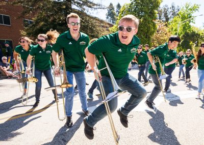 Band members jump while holding their instruments at the Open House Parade.