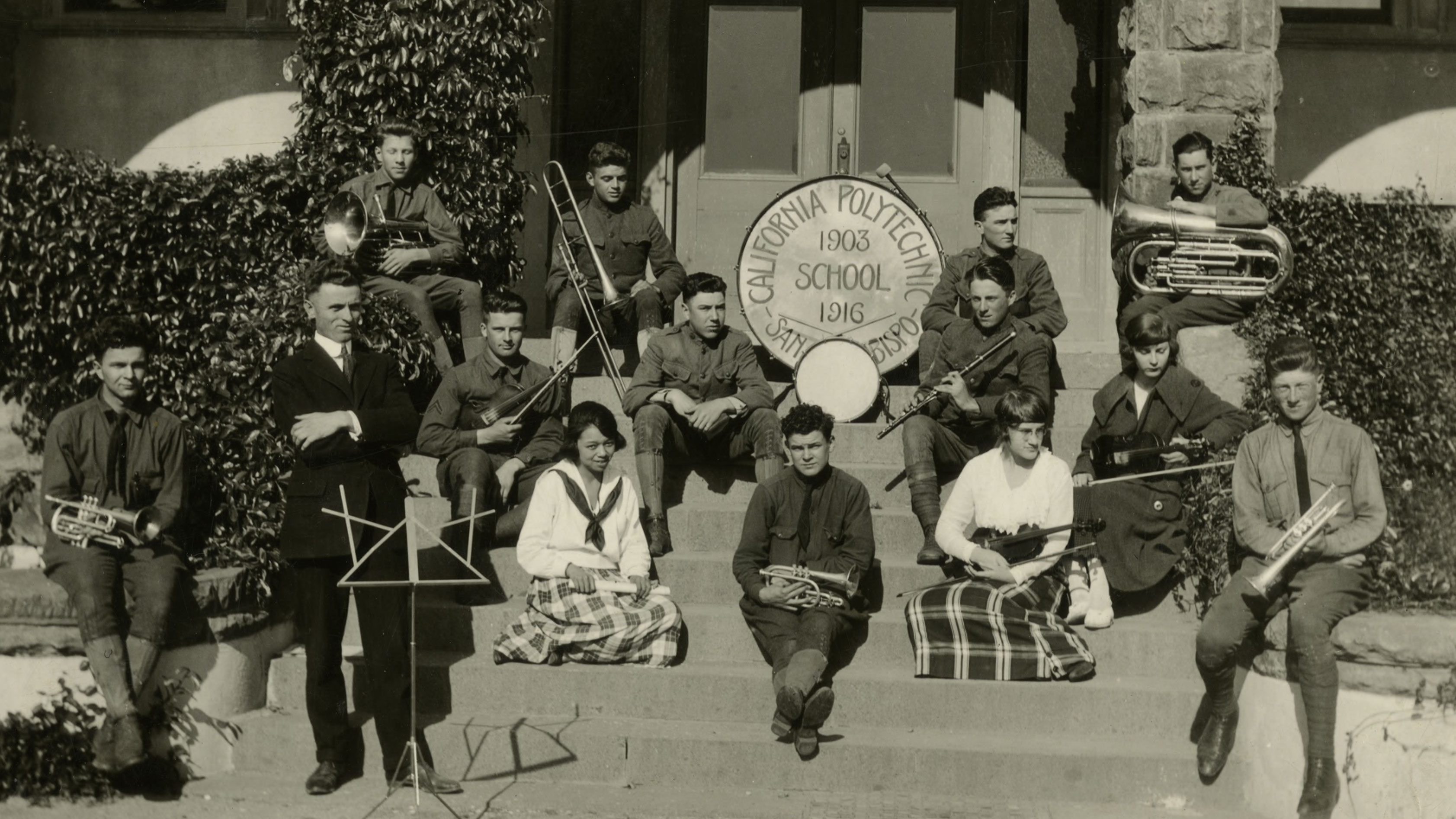 A black and white photo of 13 Cal Poly students with instruments in 1919.