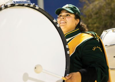 Kristine Sandoval smiles as she plays the bass drum in Mustang Band