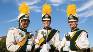 Drum majors Ben Howard, Kent Giese and Kai Quizon hold their maces before a home football game