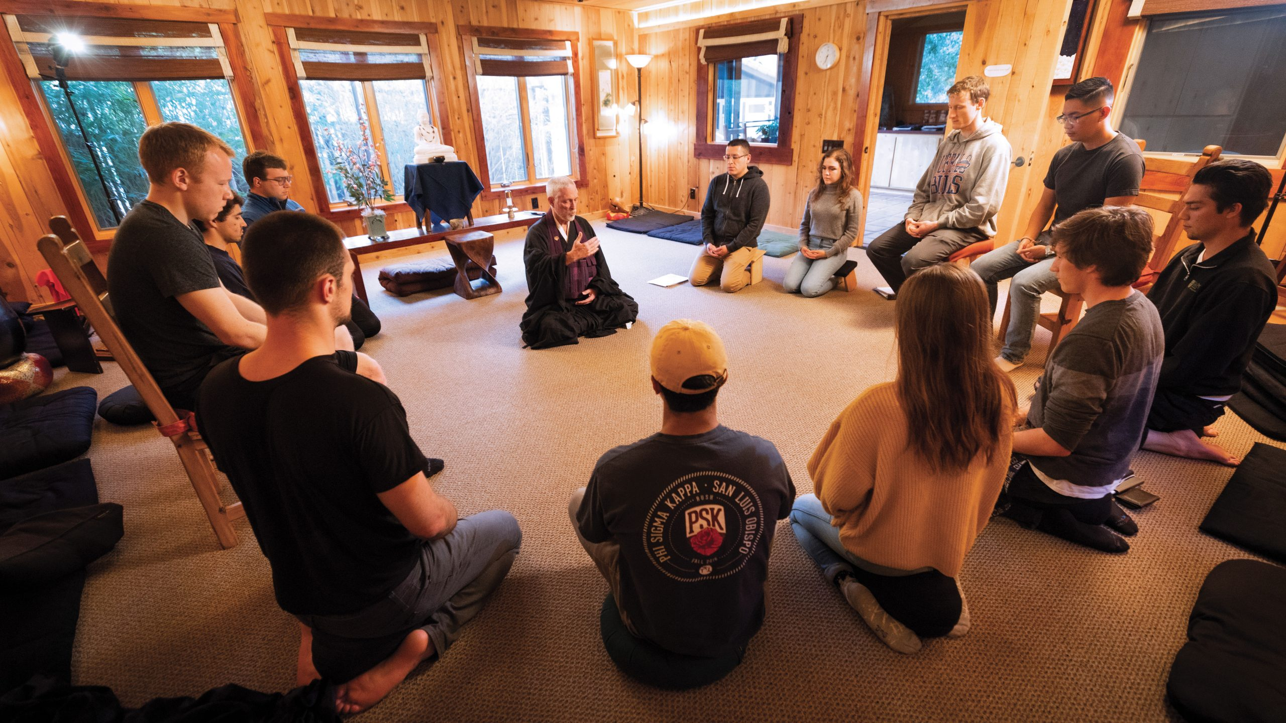 Students sit in a circle with their eyes closed around a zen priest.