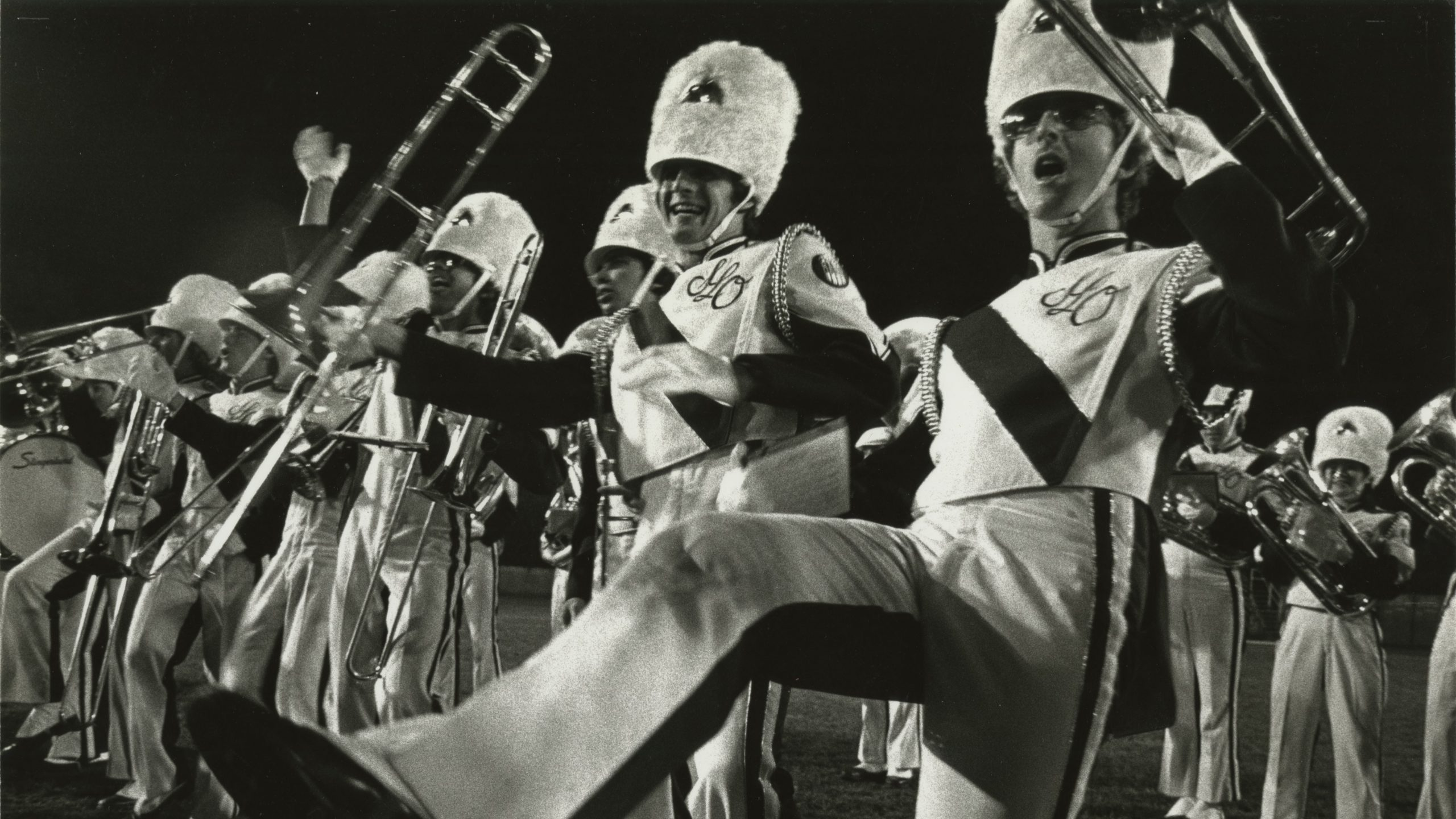A black and white photo of Mustang Band members performing in 1983.
