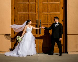 Amy Bellinghiere and Thomas Merrill Jr. hold hands on their wedding day in front of large wooden doors