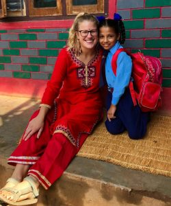 Peace Corps volunteer Sophie Bergland hugs a child in Nepal.