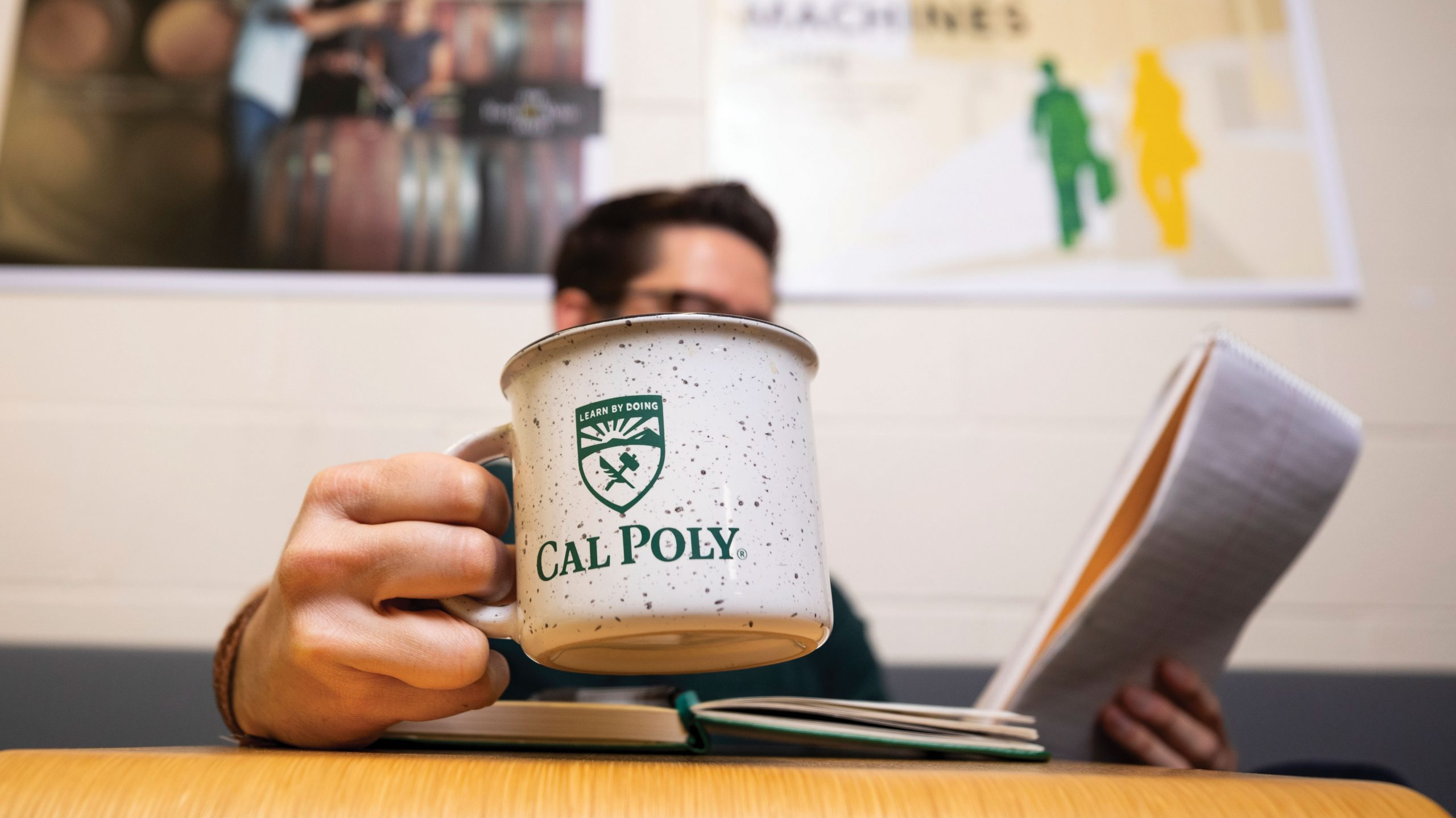 Cal Poly Magazine Editor Larry Peña holds a coffee cup in his office.