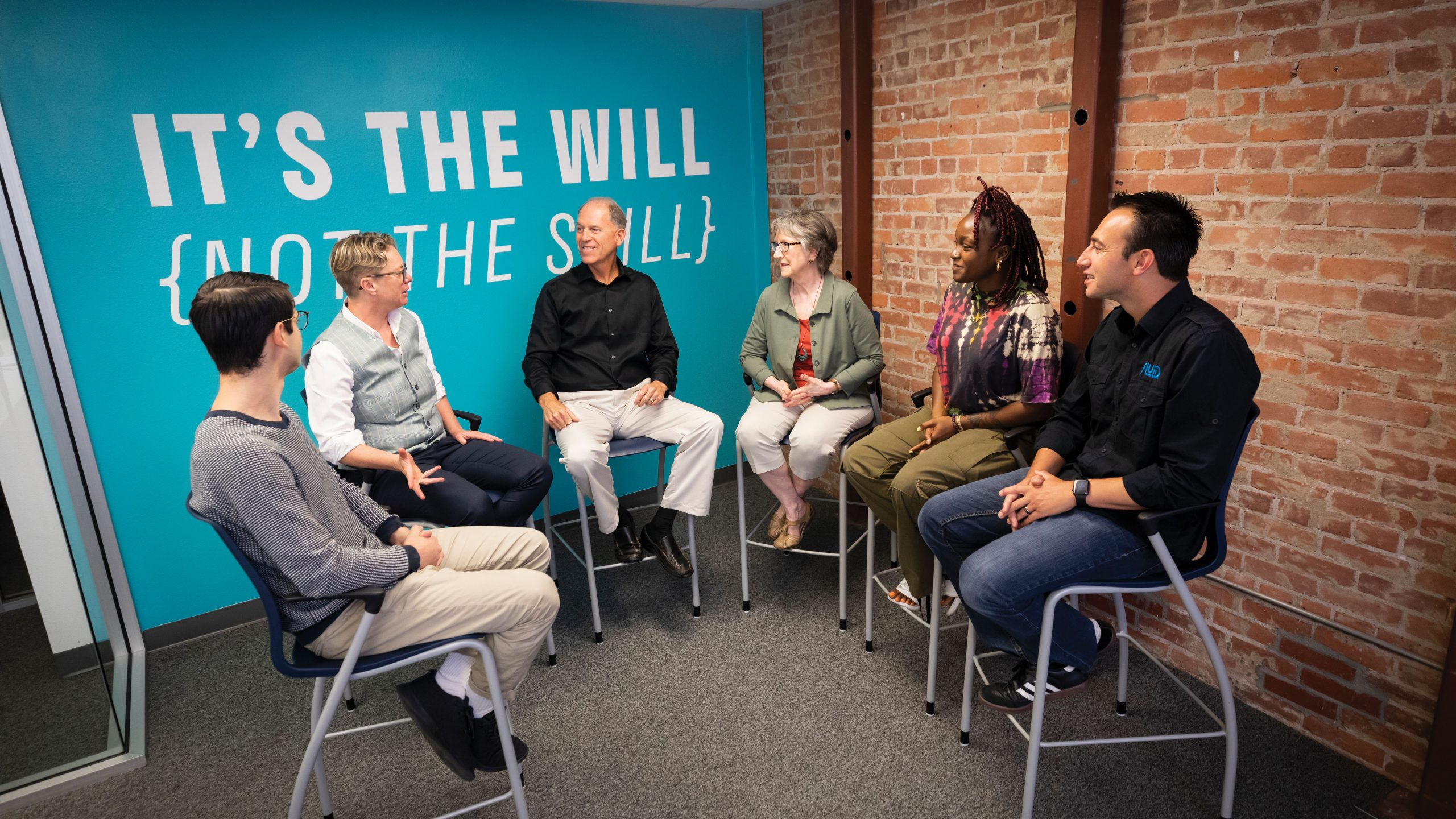 Six Cal Poly entrepreneurs sit in front of a teal wall that says 'It's the will, not the skill'
