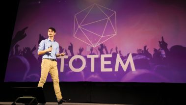 Tal Kornfeld speaks in front of a slide with the Totem logo while making a pitch during the Center for Innovation and Entrepreneurship's Demo Day event