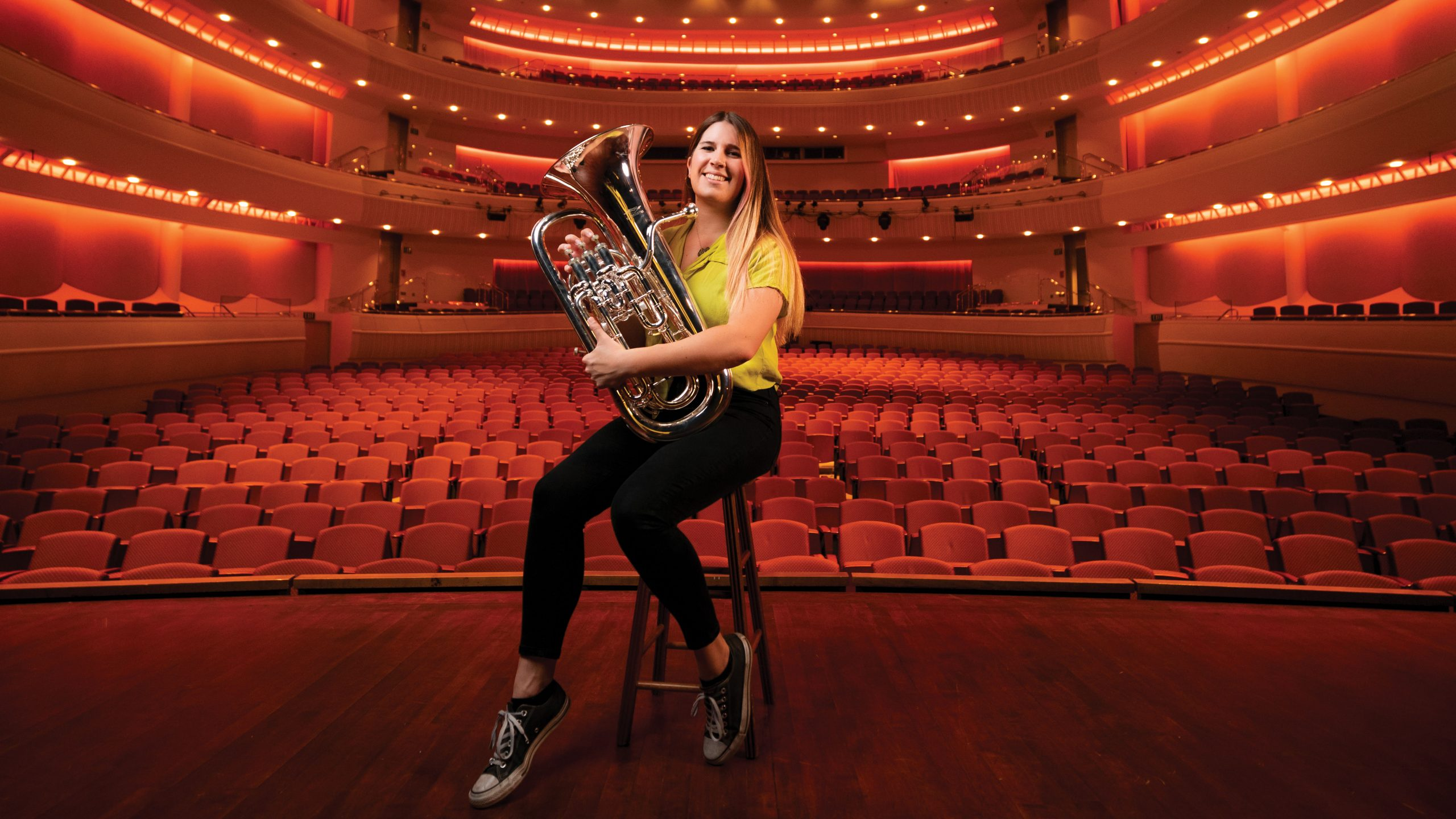 Architecture student Emma Gracyk smiles on the Performing Arts Center stage with her euphonium.