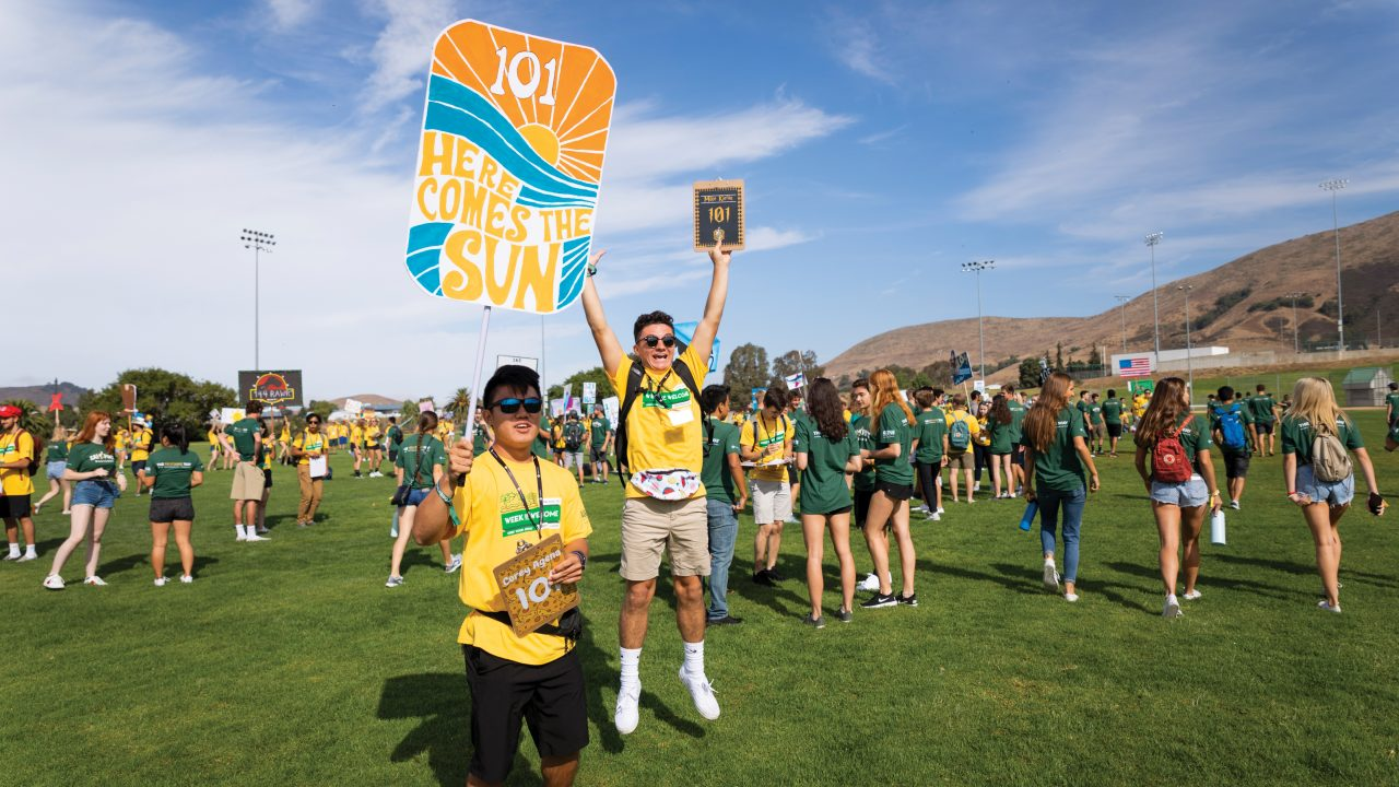 Two young men, wearing sunglasses and yellow Week of Welcome t-shirts and gesturing excitedly with signs, stand on a grassy field in front of dozens of other students.