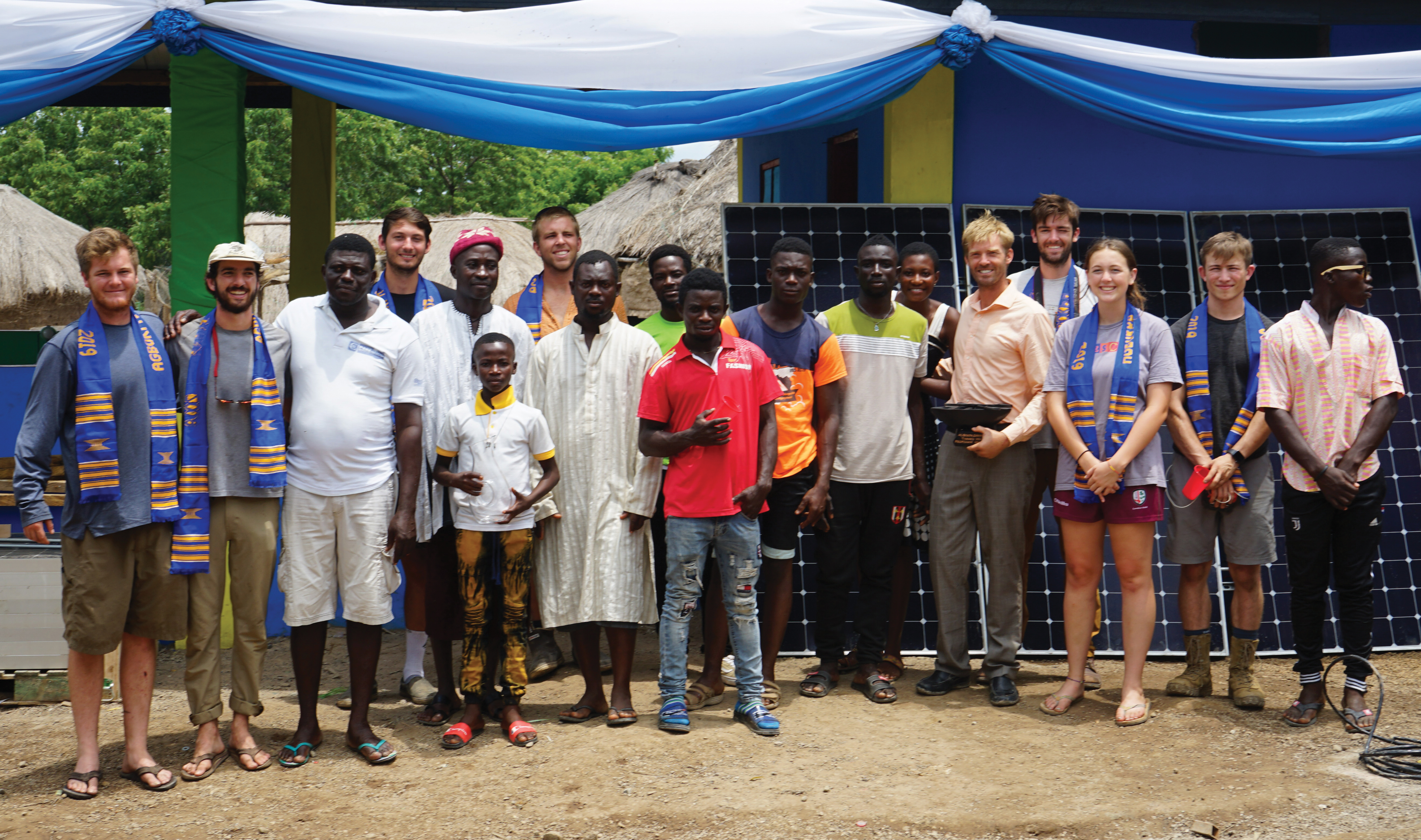 Eight Cal Poly students pose with a group of Ghanaian locals in front of a new building and a set of solar panels.