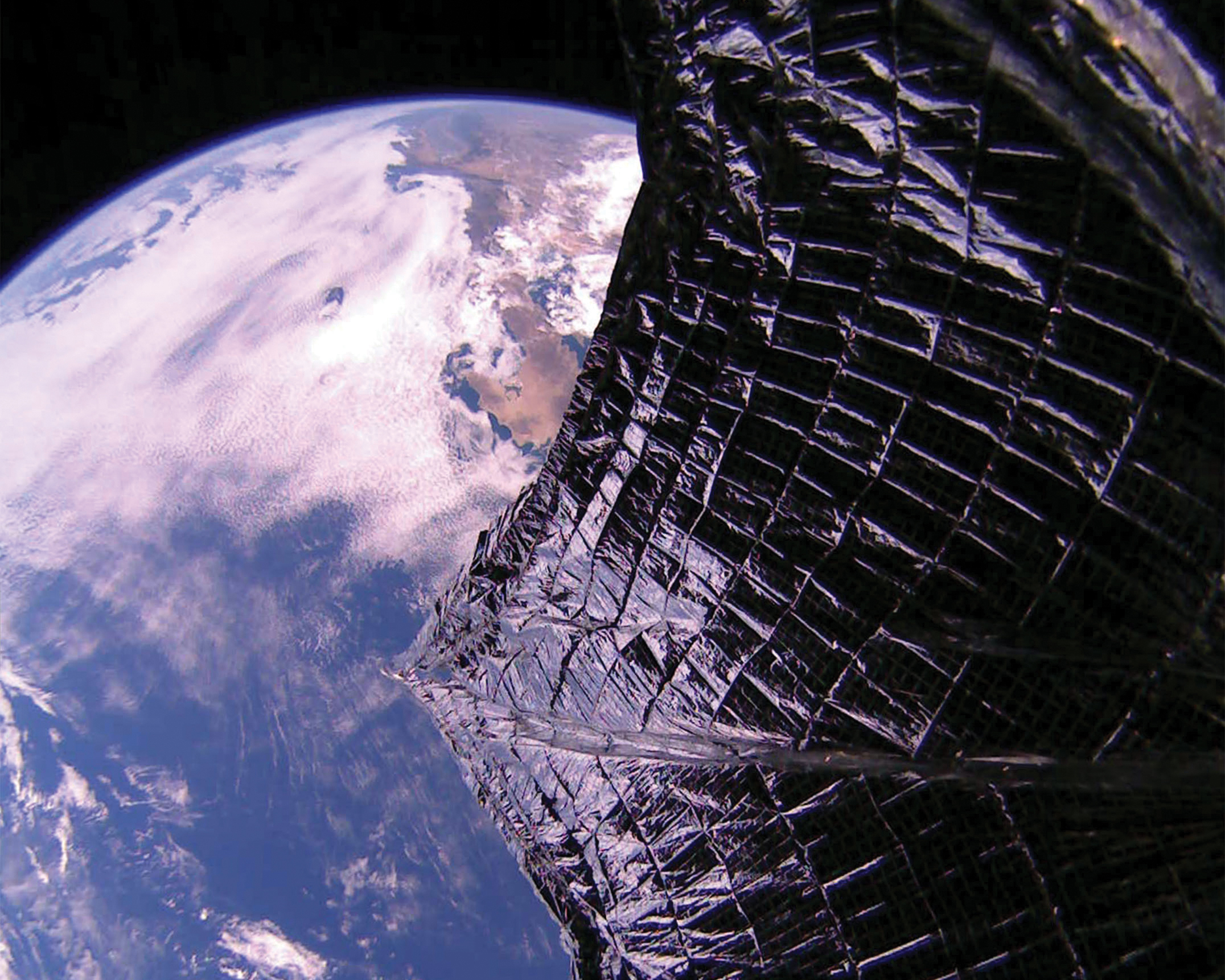 From space, a wide metal foil sail partially obscures the view of the Earth.