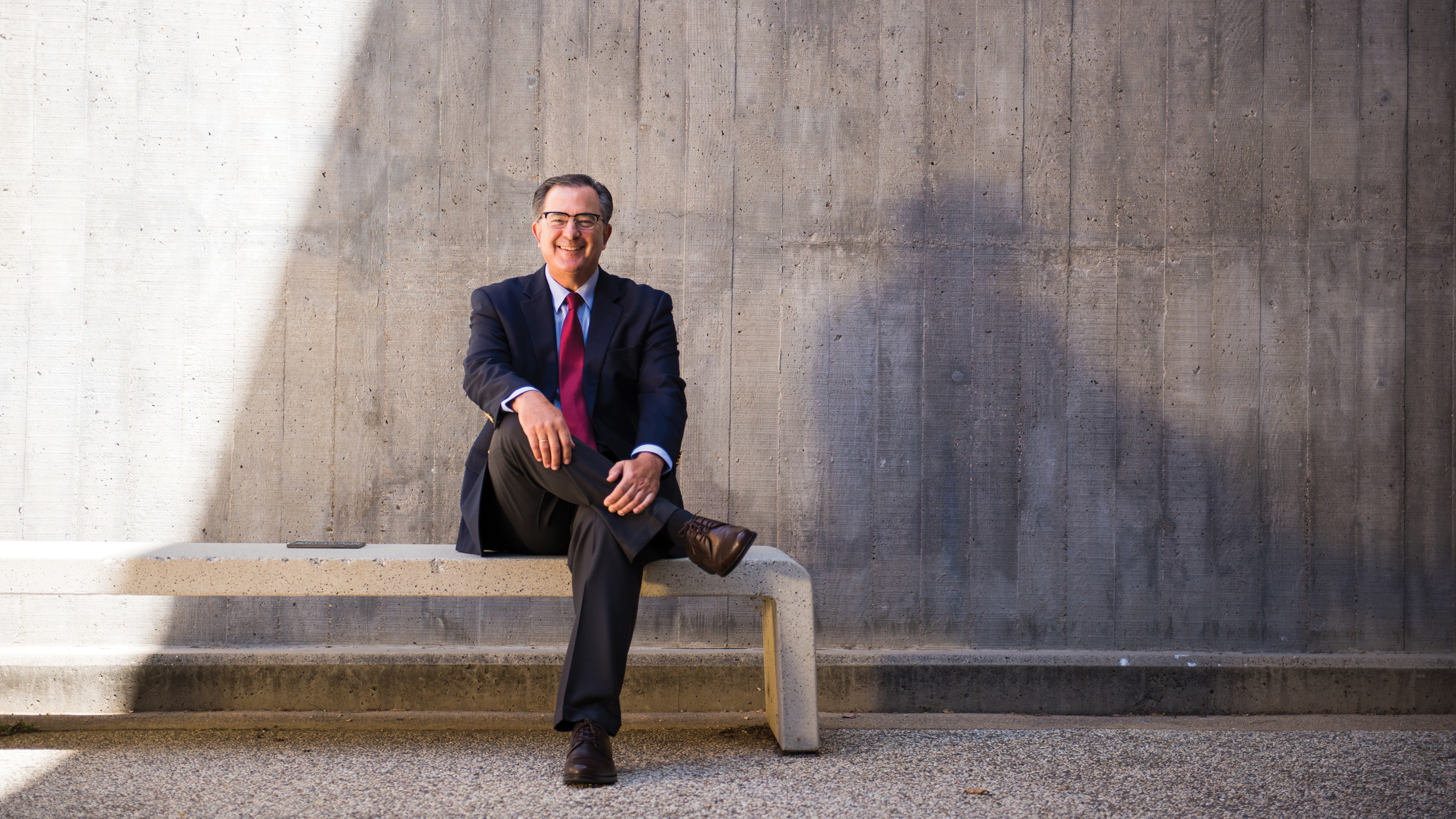 Dean Philip Williams, in a suit and tie, sits on a bench in front of a concrete wall.