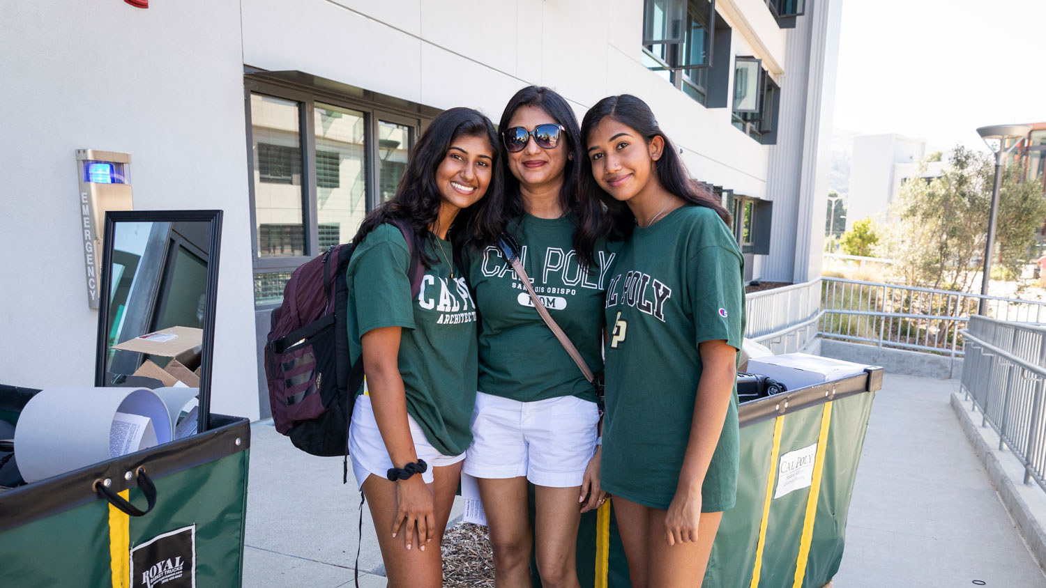 A mother and two daughters all in Cal Poly t-shirts smile in front of the yakʔitʸutʸu residence halls.