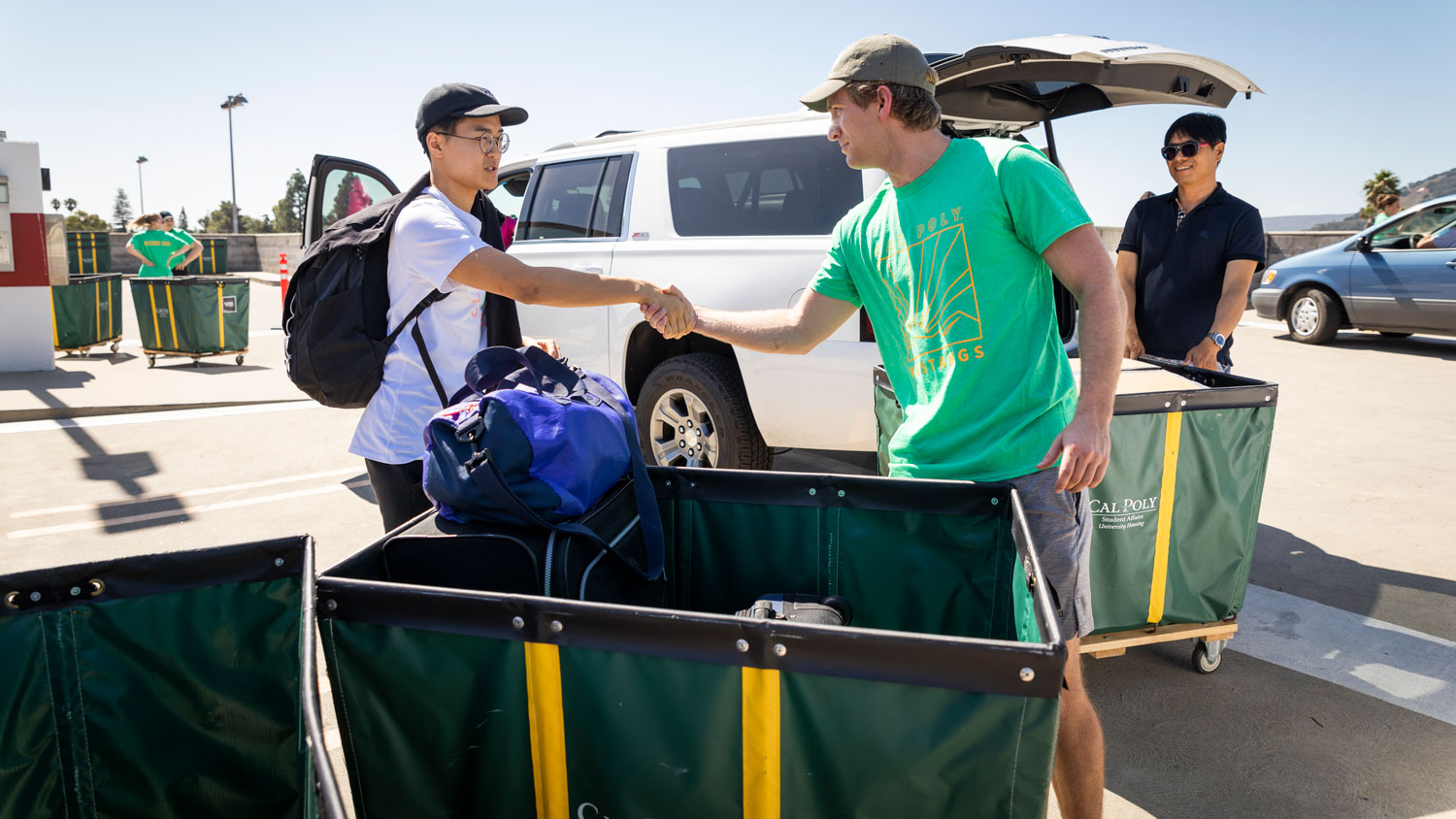 A new Cal Poly student and a volunteer shake hands while loading a cart on move-in day