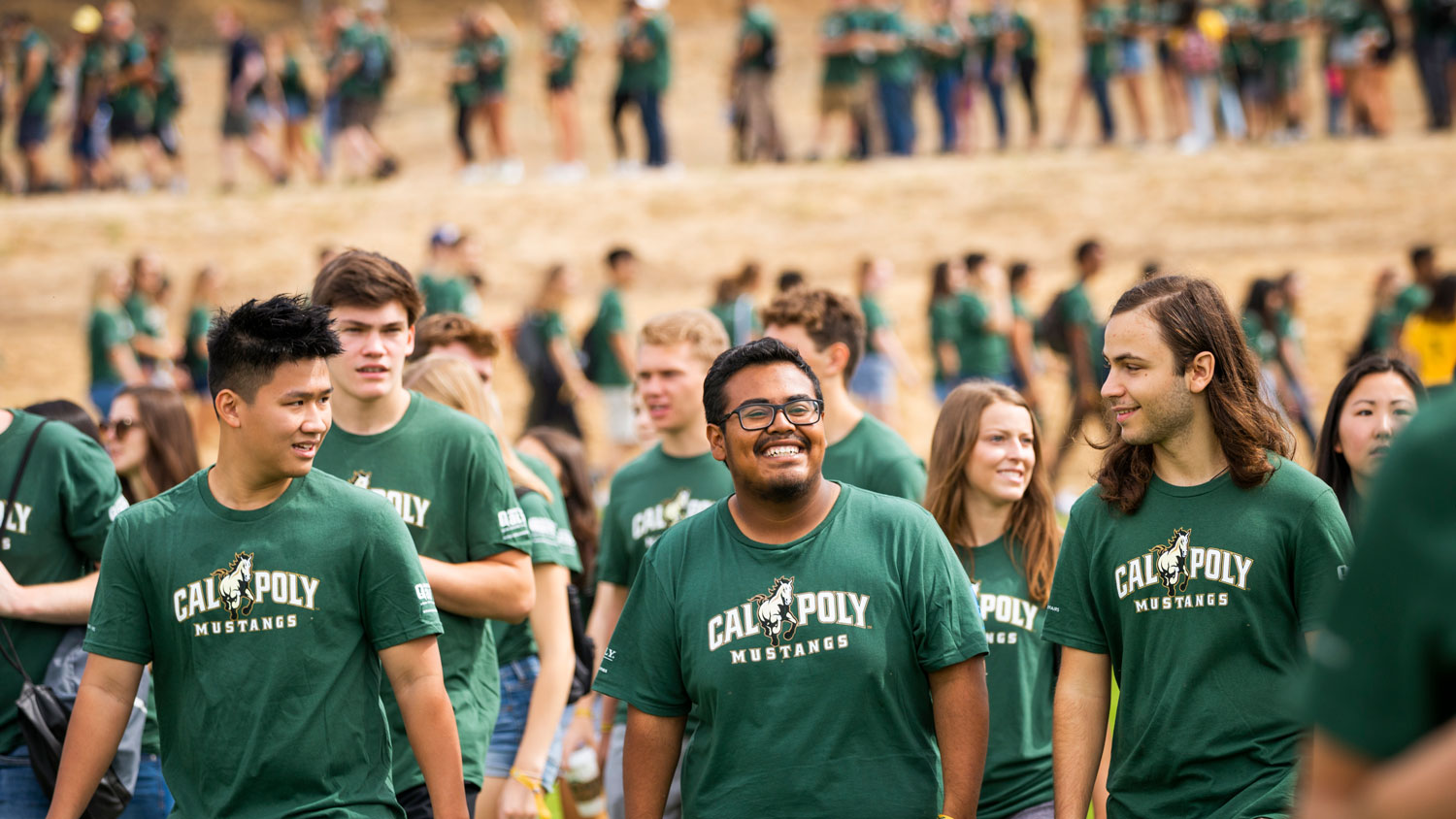 Three Cal Poly students walk toward the Week of Welcome event.