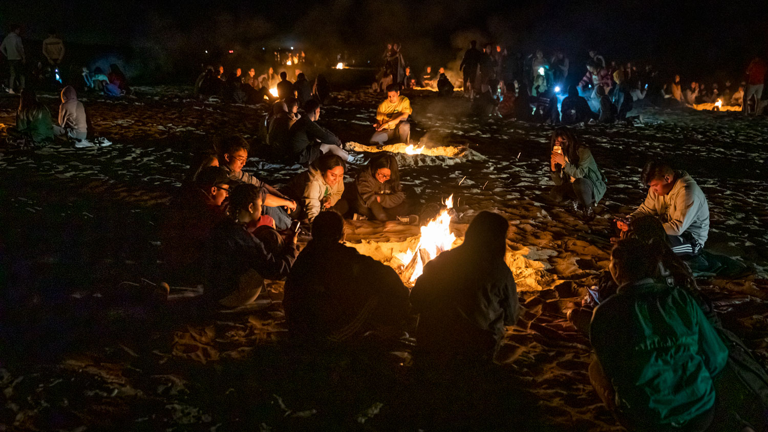 Several WOW groups surround bonfires at Grover Beach.