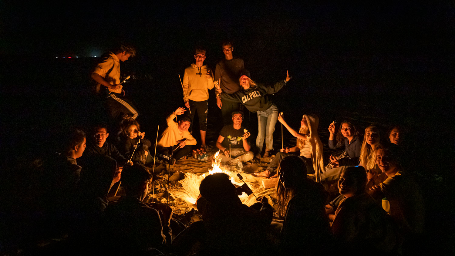 Students smile around a WOW group bonfire at Grover Beach