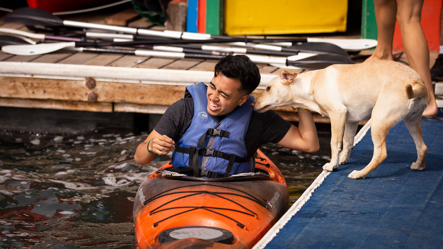 A dog sniffs a student sitting in kayak in Morro Bay