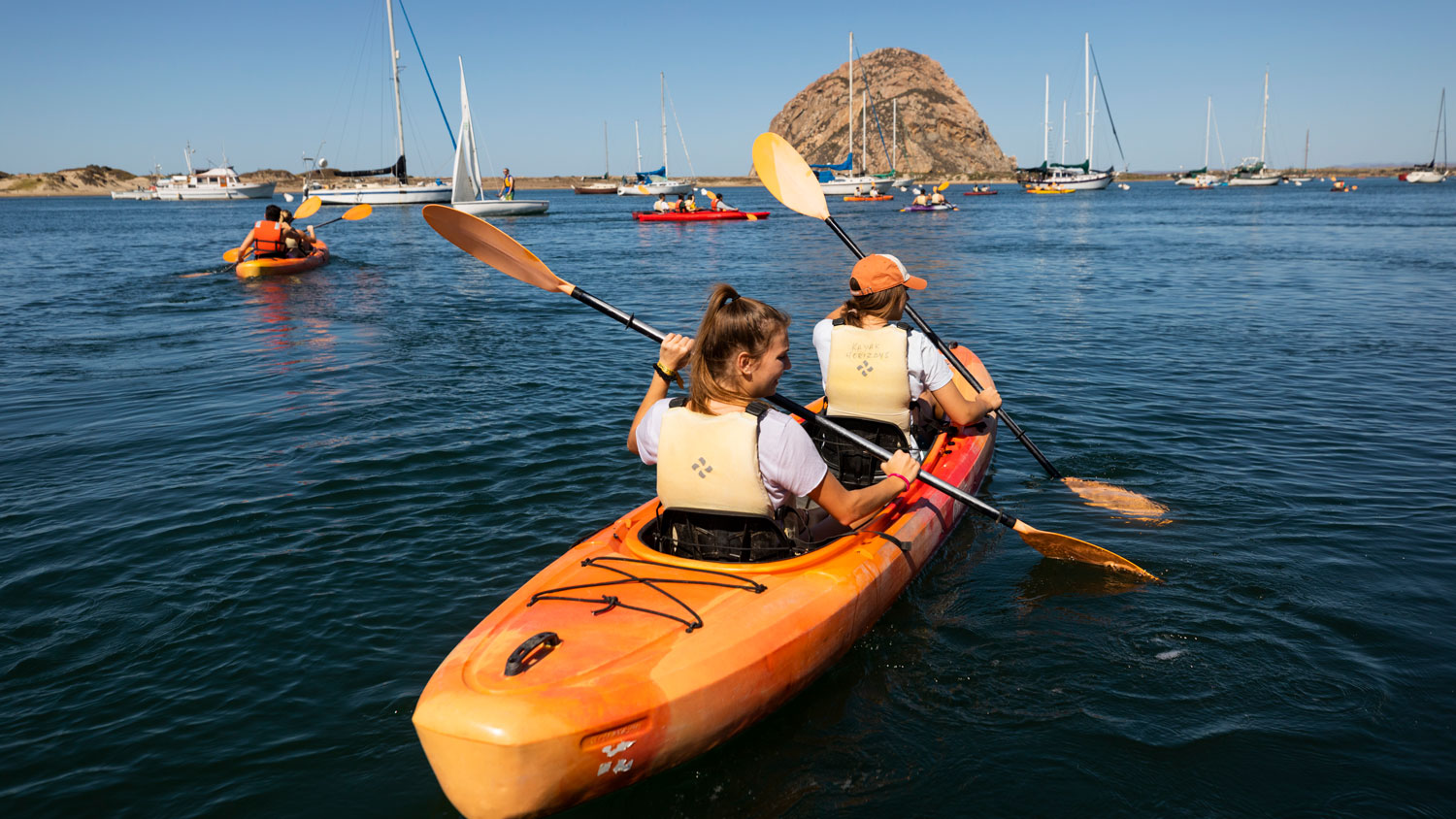 Cal Poly students paddle a double kayak toward Morro Rock