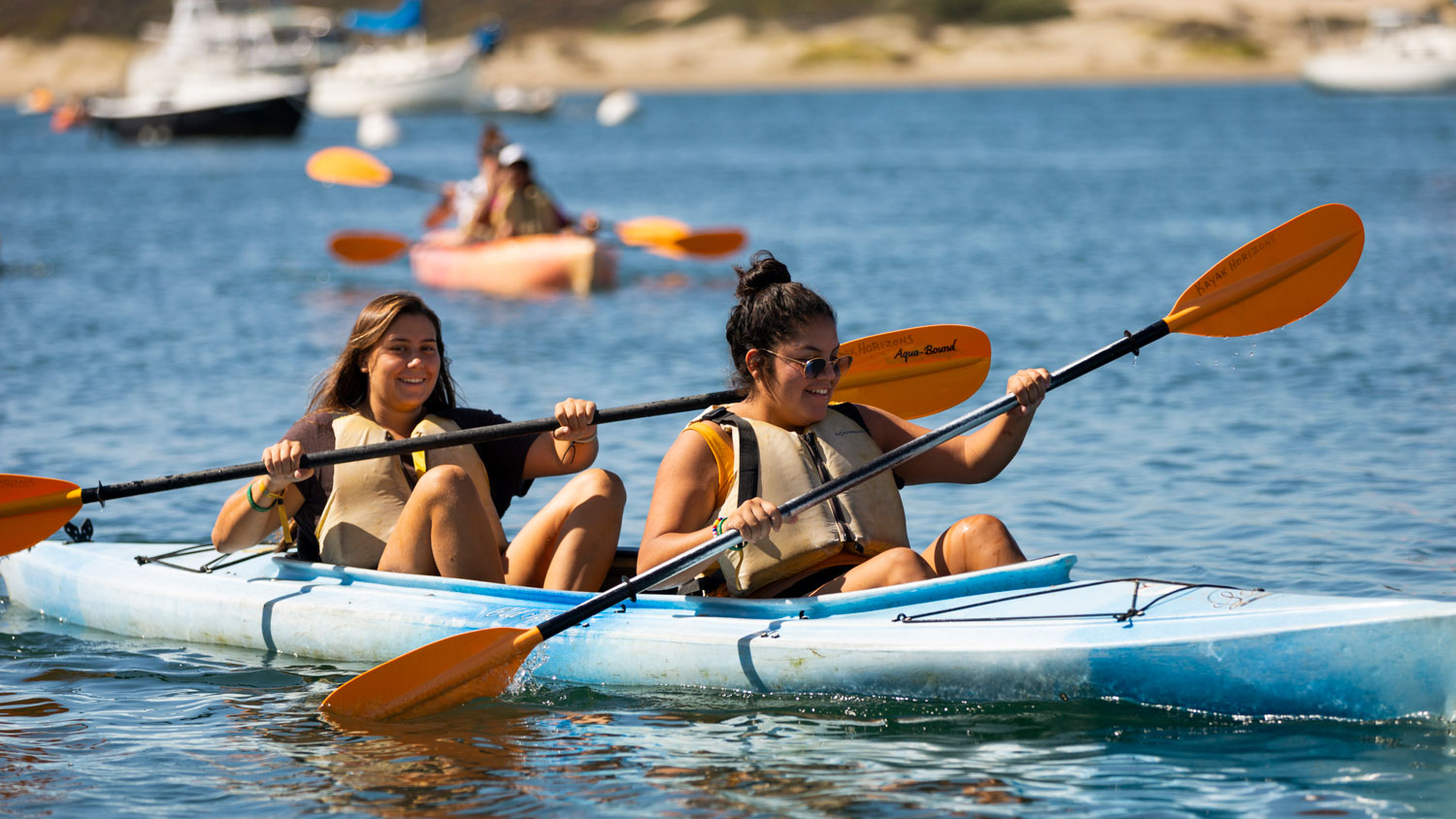 Two female students paddle a kayak in Morro Bay during Week of Welcome