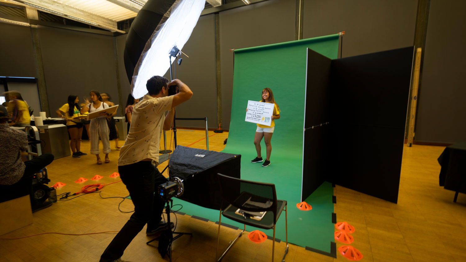 A student poses with a white board for the I Am Cal Poly project while a photographer takes their photo