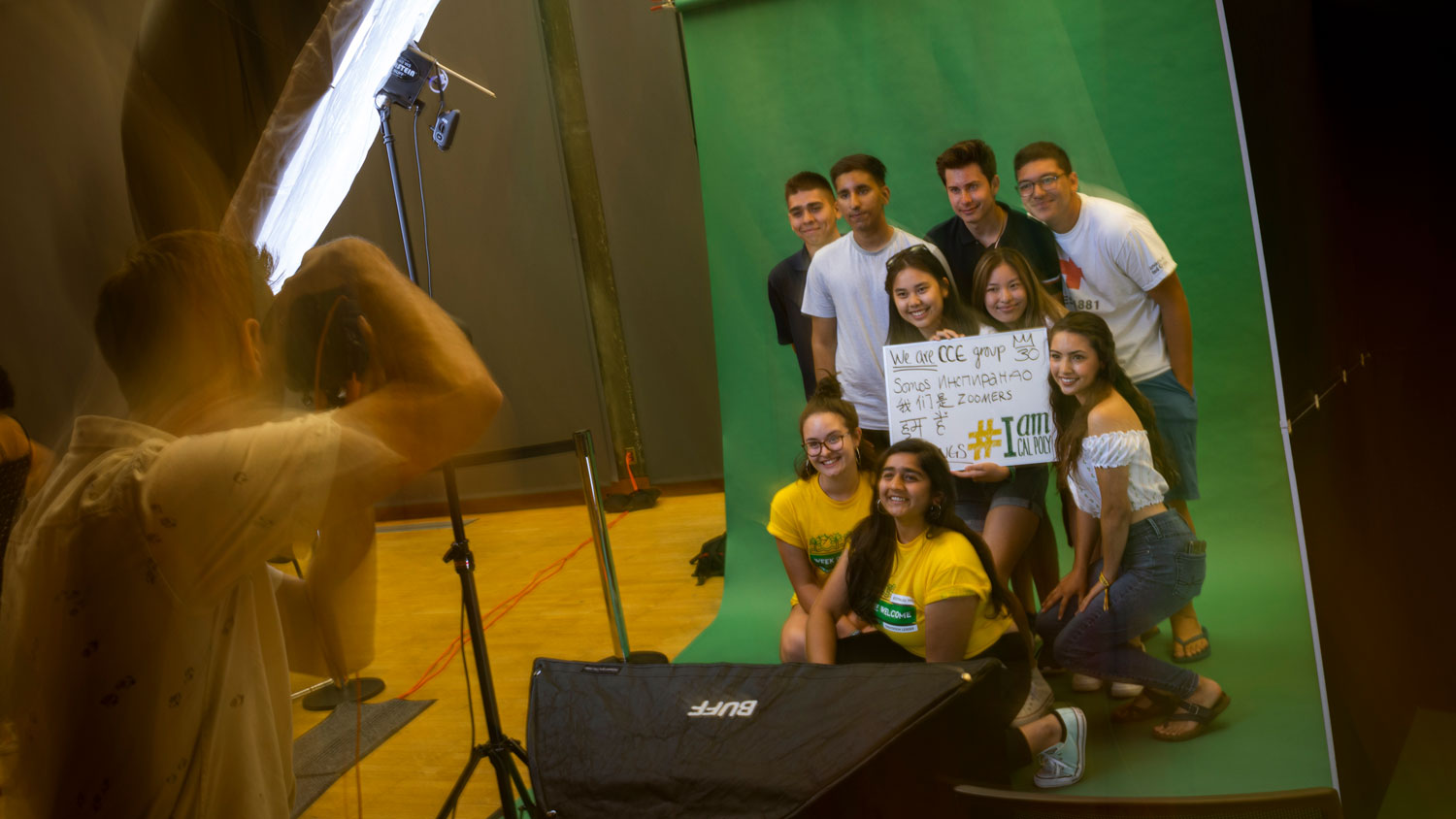 A group of students holds a sign while having her photo taken for the I Am Cal Poly project
