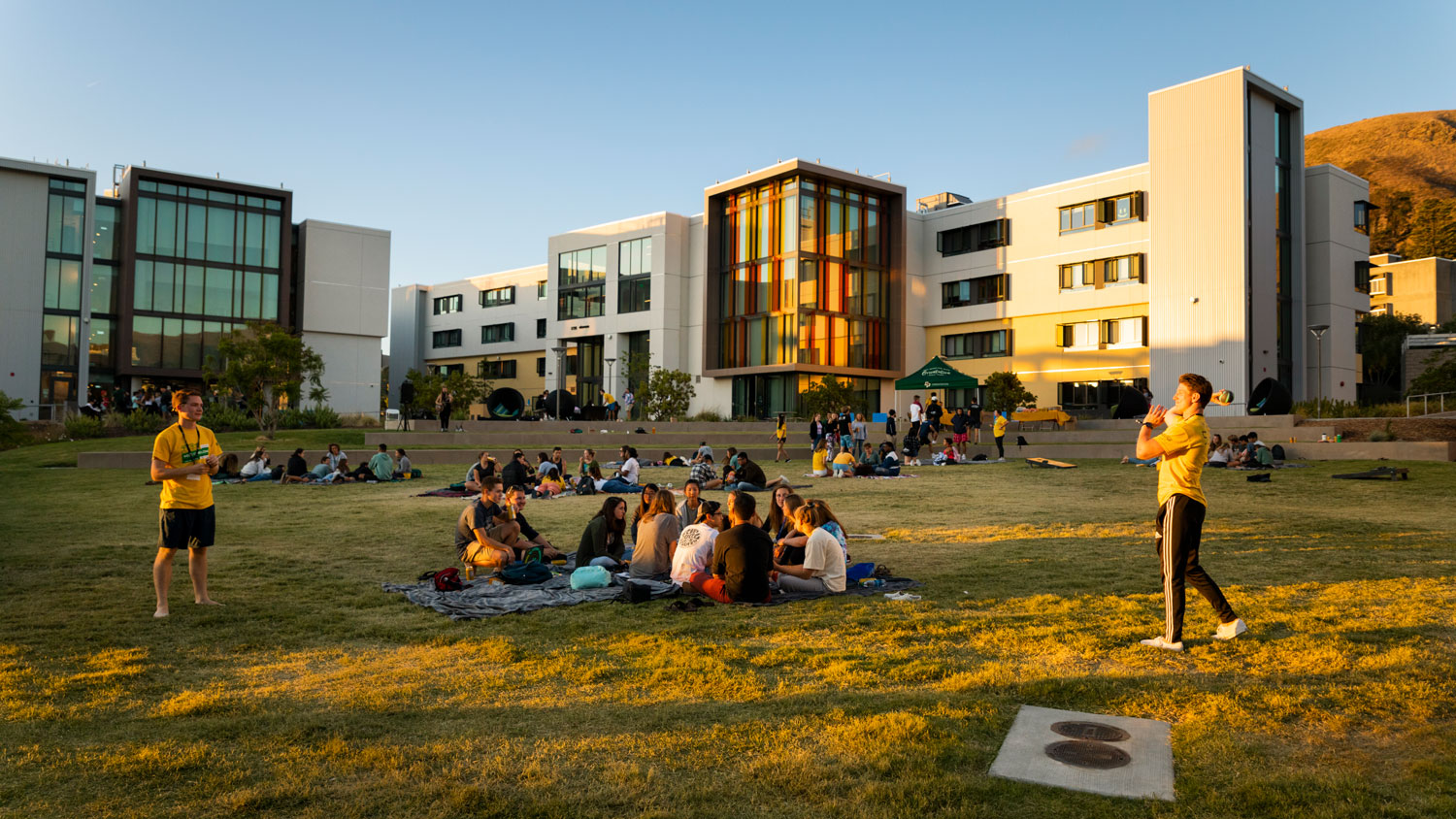 Cal Poly students listen to an accoustic concert on campus during sunset.