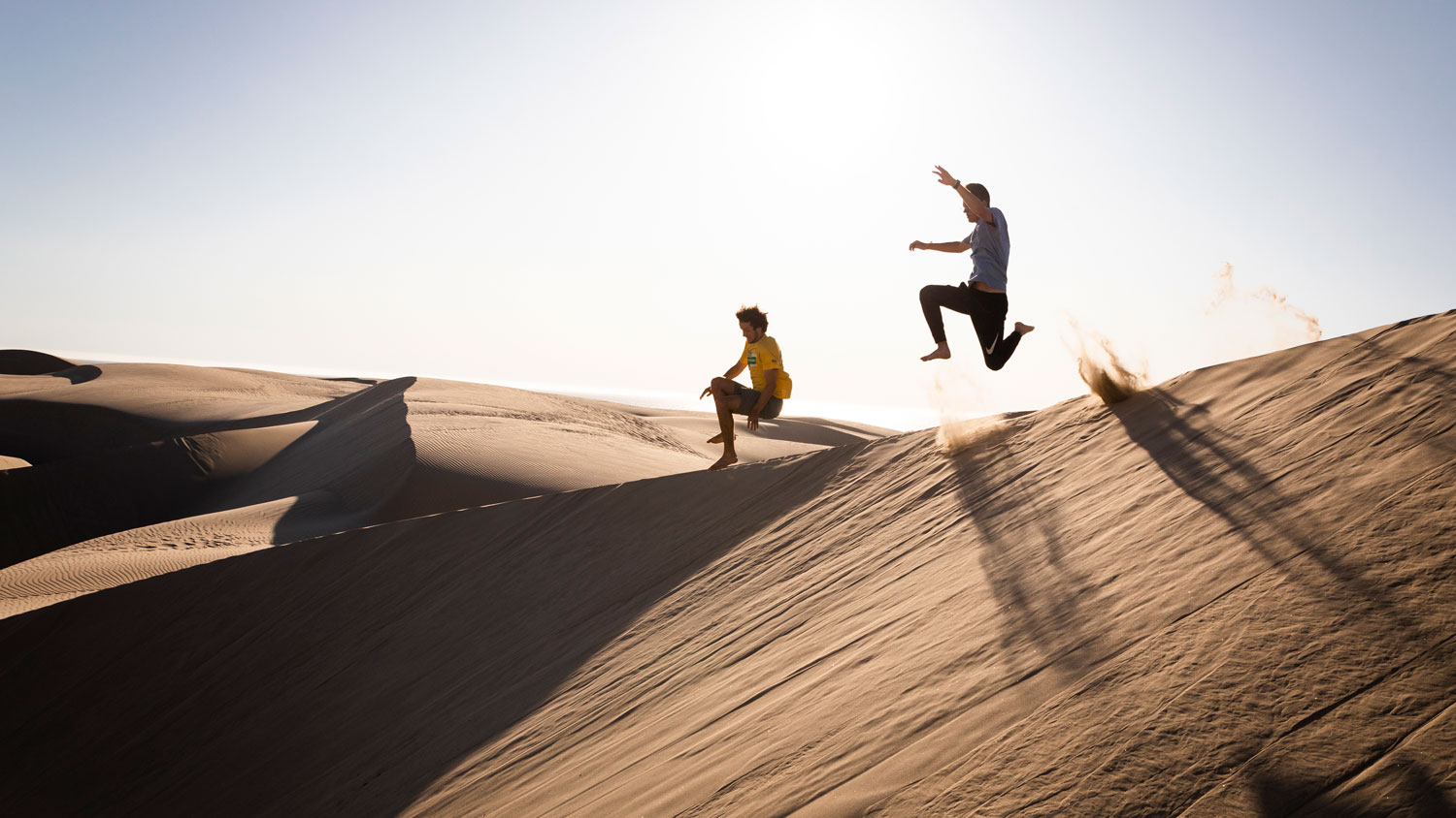 Students jump off the edge of a dune in Oceano during WOW.