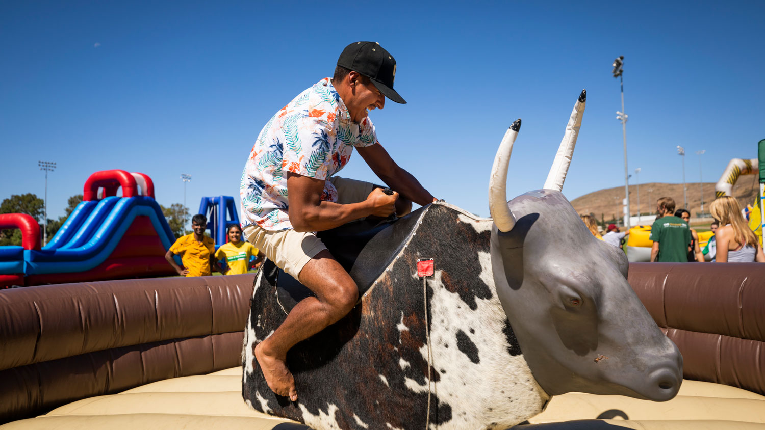 A student in a black hat rides a mechanical bull at Week of Welcome's Inflate-a-Fest