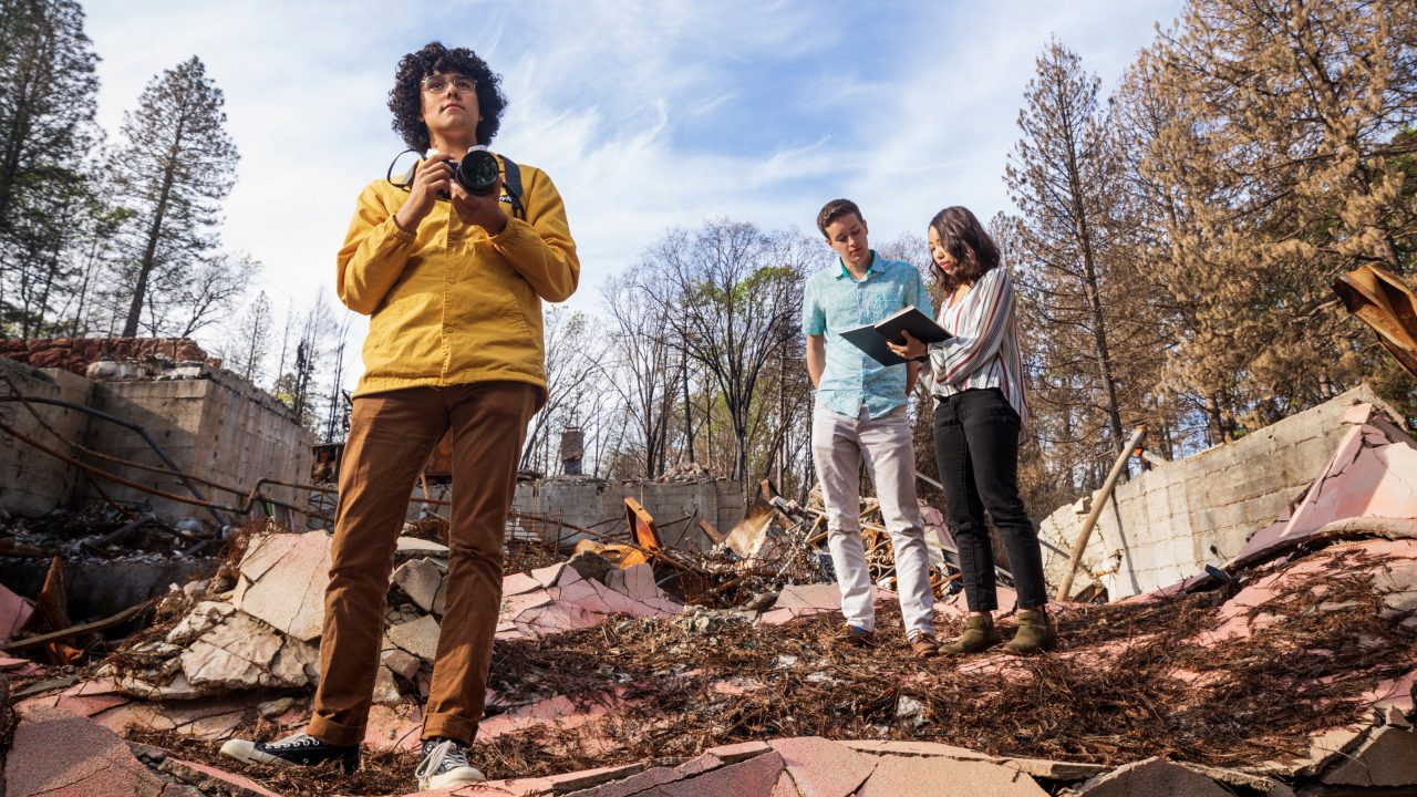 Three Cal Poly architecture students stand in the rubble of a home in Paradise, California, after the Camp Fire.